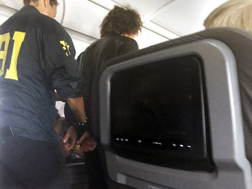 In this photo provided by Donna Basden, a man is escorted off an American Airlines flight after it landed in Honolulu, Friday, May 19, 2017. Federal agents met the plane from Los Angeles when it landed in Honolulu and took the man into custody. (Donna Basden via AP)