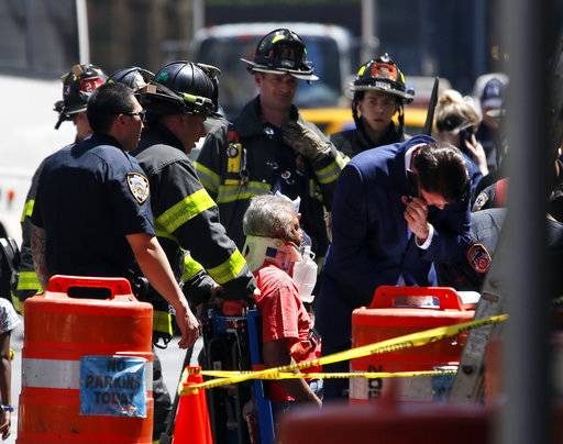 Emergency personnel treat a victim after a car ploughed through a crowd of pedestrians during lunchtime at New York's Times Square, Thursday, May 18, 2017. Police do not suspect a link to terrorism and the driver was taken into custody to be tested for alcohol.