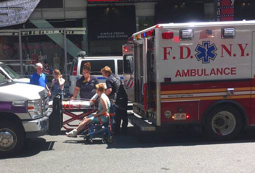 First responders assist one of the victims of a car crash, Thursday, May 18, 2017 in New York.  A man who appeared intoxicated drove his car the wrong way up a Times Square street and plowed into pedestrians on the sidewalk injuring dozens authorities and witnesses said.