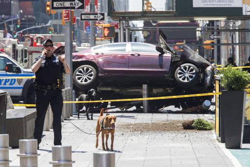 Investigators works at the scene of a car crash, Thursday, May 18, 2017, in New York's Times Square.   A man who appeared intoxicated drove his car the wrong way up the Times Square street and plowed into pedestrians on the sidewalk injuring dozens authorities and witnesses said.