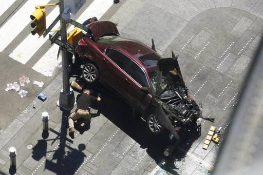 A police officer inspects a car crash, Thursday, May 18, 2017, in New York's Times Square.   A man who appeared intoxicated drove his car the wrong way up the Times Square street and plowed into pedestrians on the sidewalk injuring dozens authorities and witnesses said.