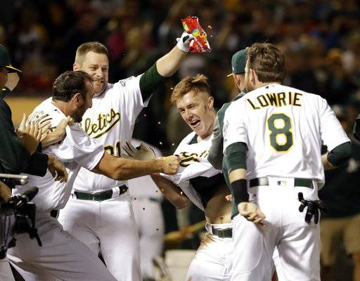Oakland Athletics' Mark Canha, center, is mobbed by teammates at home plate after his solo walk-off home run during the 10th inning of a baseball game against the Boston Red Sox on Friday, May 19, 2017, in Oakland, Calif. Oakland won 3-2. (AP Photo/Marcio Jose Sanchez)