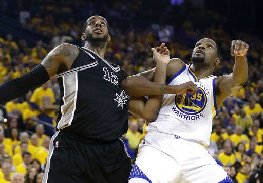 San Antonio Spurs' LaMarcus Aldridge (12) and Golden State Warriors' Kevin Durant (35) work for position under the basket during the second half of Game 2 of the NBA basketball Western Conference finals, Tuesday, May 16, 2017, in Oakland, Calif. (AP Photo/Marcio Jose Sanchez)