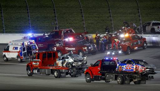 The cars of Danica Patrick (10) and Joey Logano (22) are hauled past rescue efforts for Aric Almirola, back, during the NASCAR Monster Cup auto race at Kansas Speedway in Kansas City, Kan., Saturday, May 13, 2017.