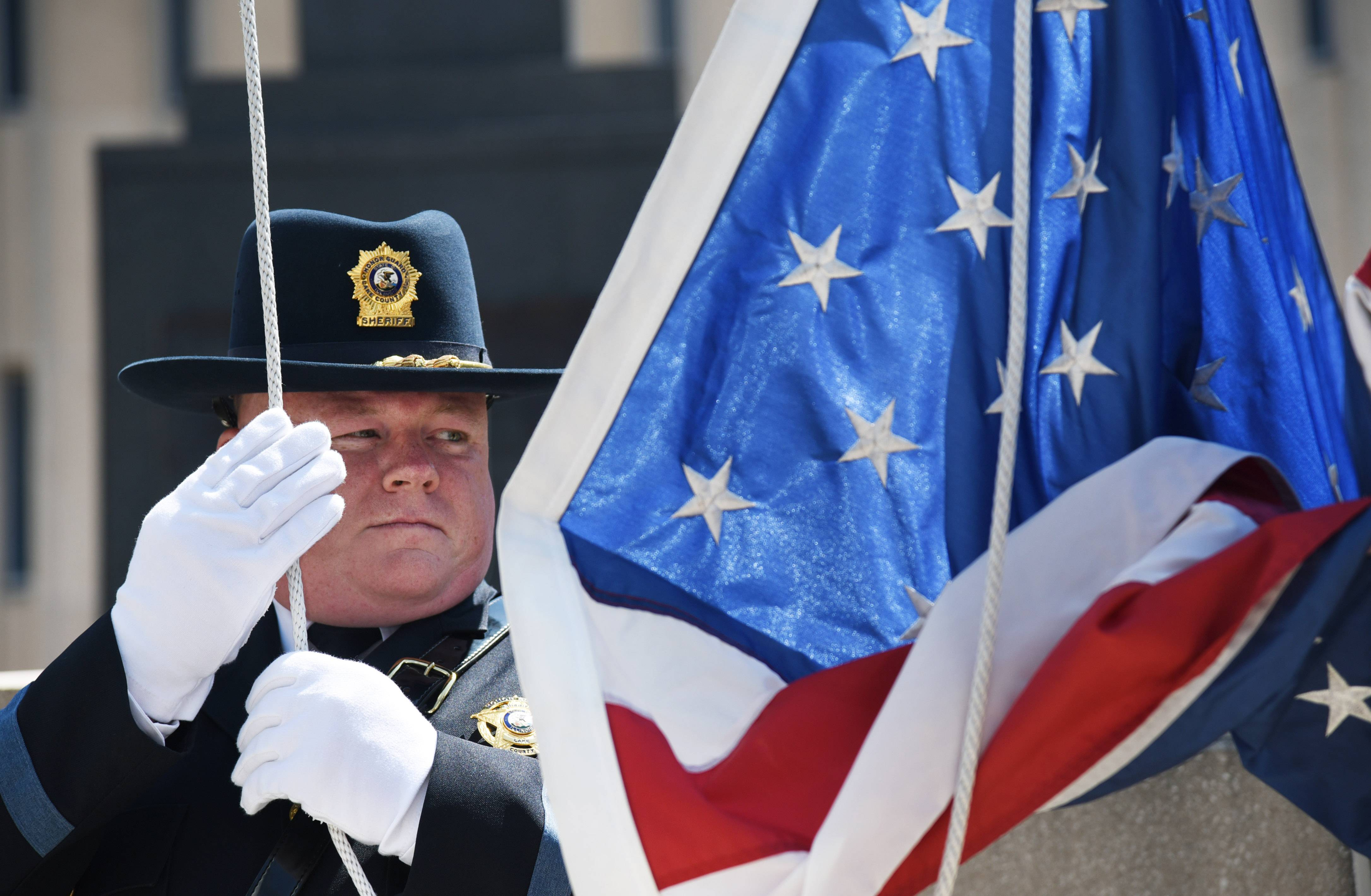 Sheriff's Deputy John Willer prepares to raise the American Flag during the Lake County 2017 Police Memorial in the Lincoln Memorial Plaza outside of the Lake County Courthouse Friday.