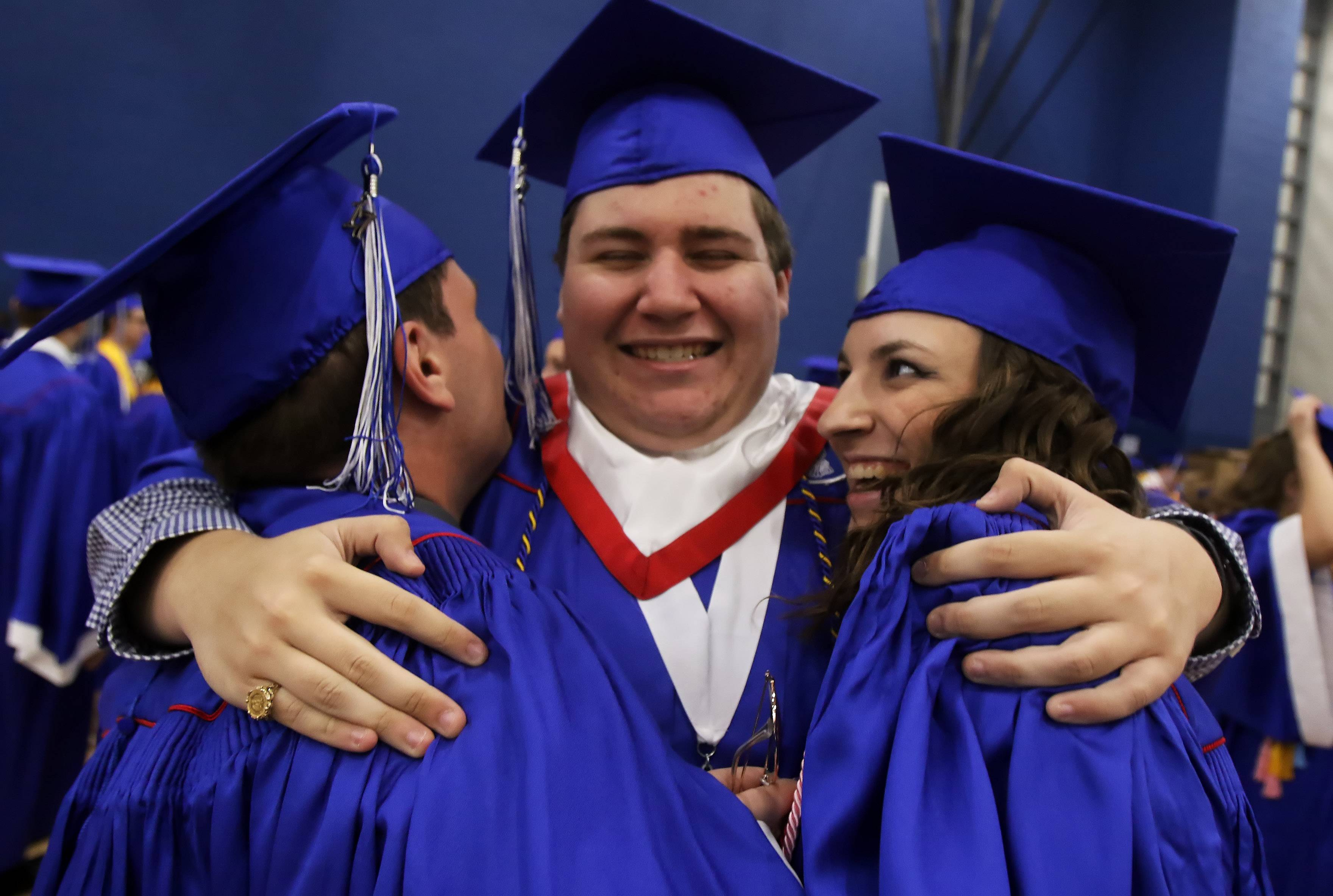 Ethan Carlson, Tyler Brumm and Joanne Gorski hug before the Lakes Community High School graduation Sunday in Lake Villa. There were 370 seniors who received their diploma at the commencement exercises.