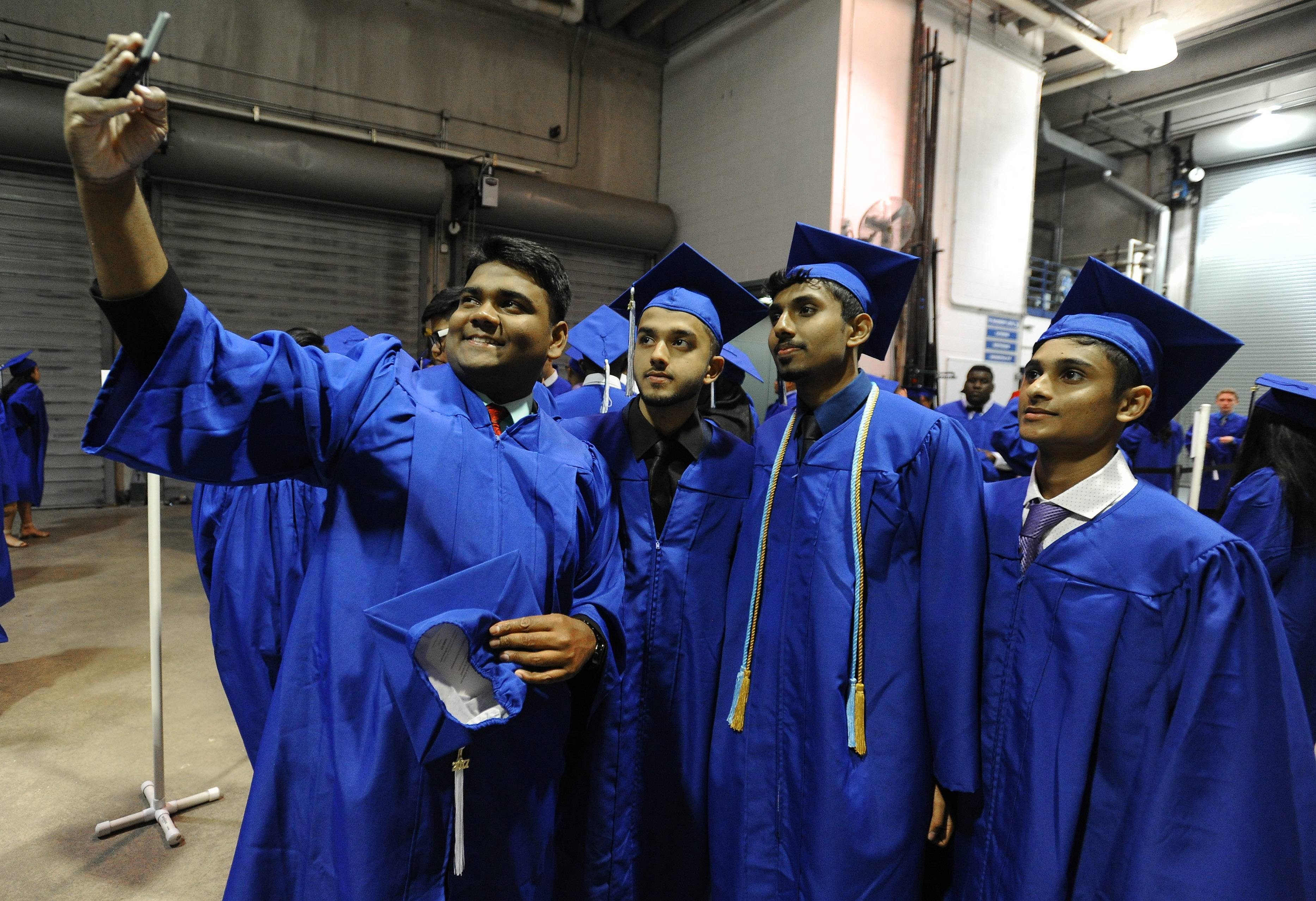 Maine East seniors Joel Shaji, 18, of Des Plaines takes a picture with his friends Sohail Khan, 19, of Skokie, Amal Josy, 18, of Des Plaines and Joseph Jacob, 18, of Des Plaines at Maine East's 150th annual commencement at the Rosemont Theatre on Sunday.