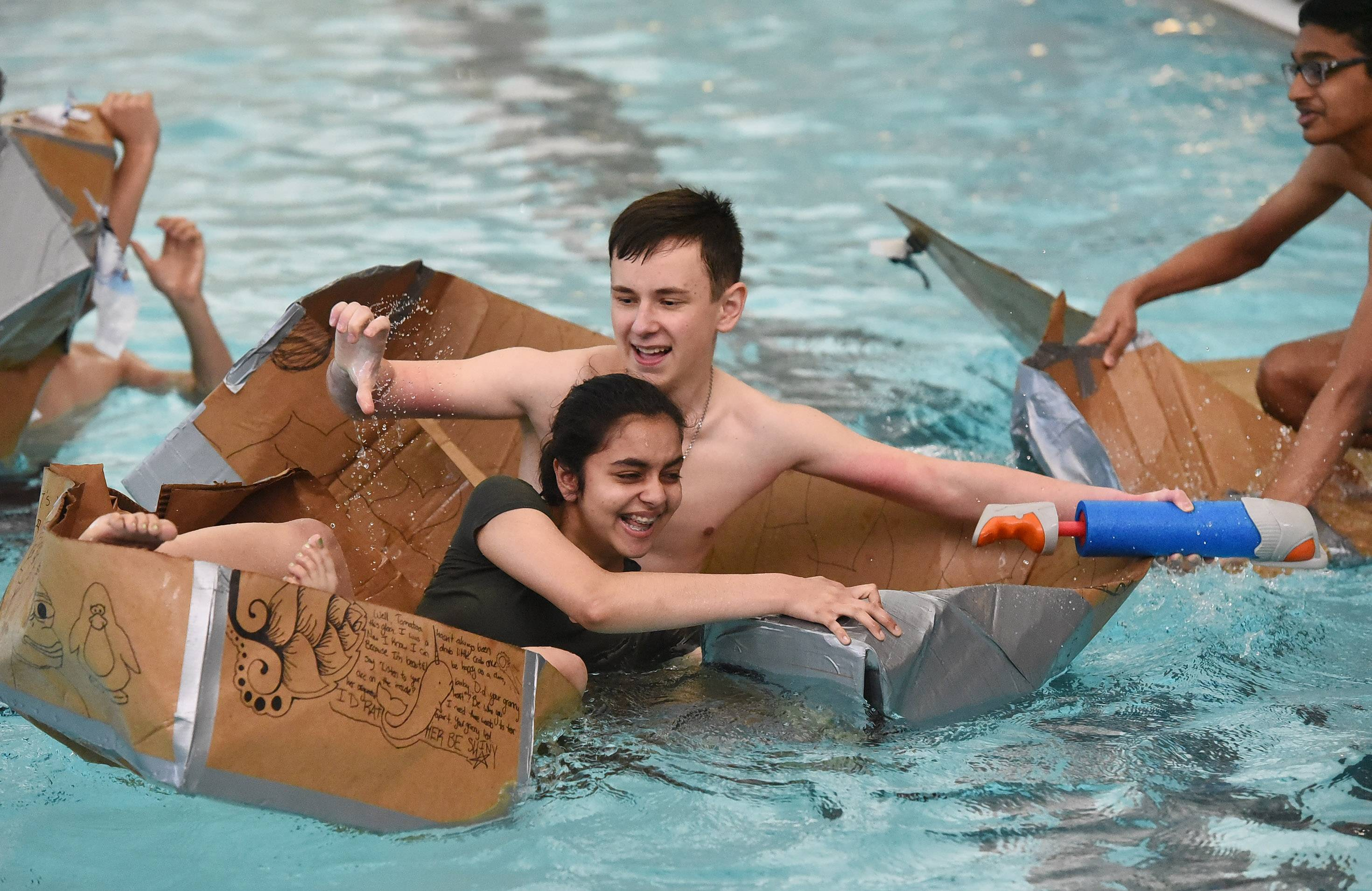 Ananya Shah and Andriy Bilobokyy struggle to stay afloat Monday during a cardboard boat regatta at Stevenson High School in Lincolnshire.