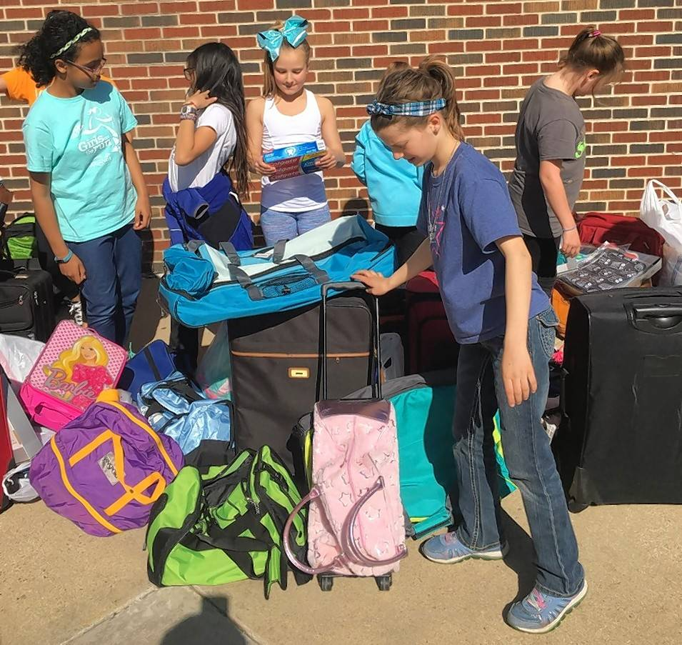 Members of the fifth-grade Girl Scout troop at Virginia Lake School in Palatine prepare collected suitcases and toiletries for pickup by DCFS.