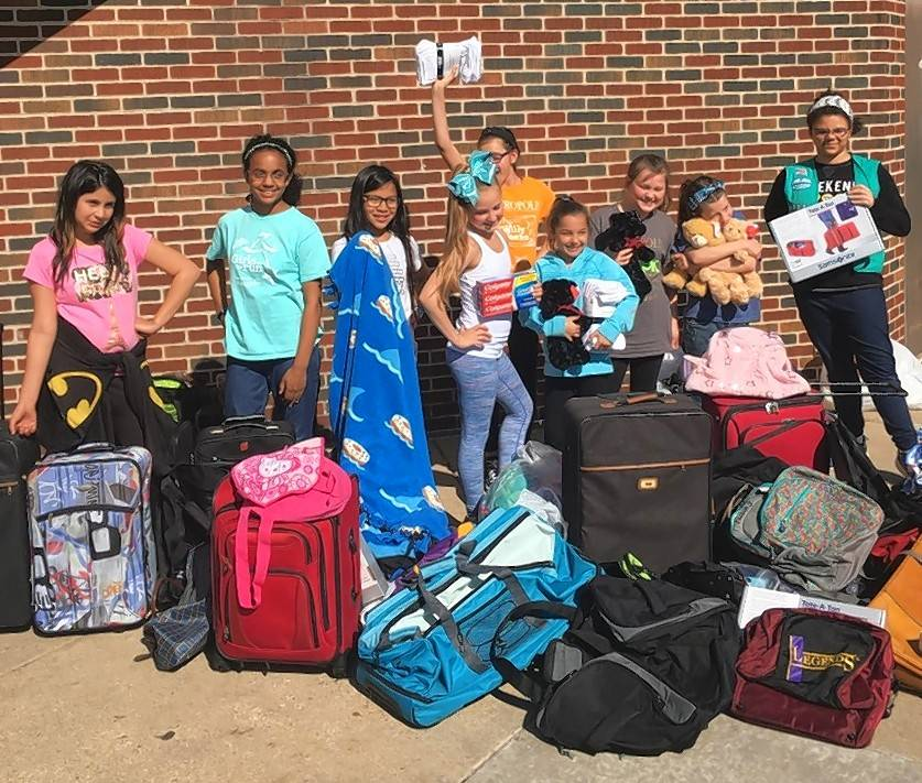Members of the fifth-grade Girl Scout troop at Virginia Lake School in Palatine celebrate their successful collection, which was lauded by DCFS officials.