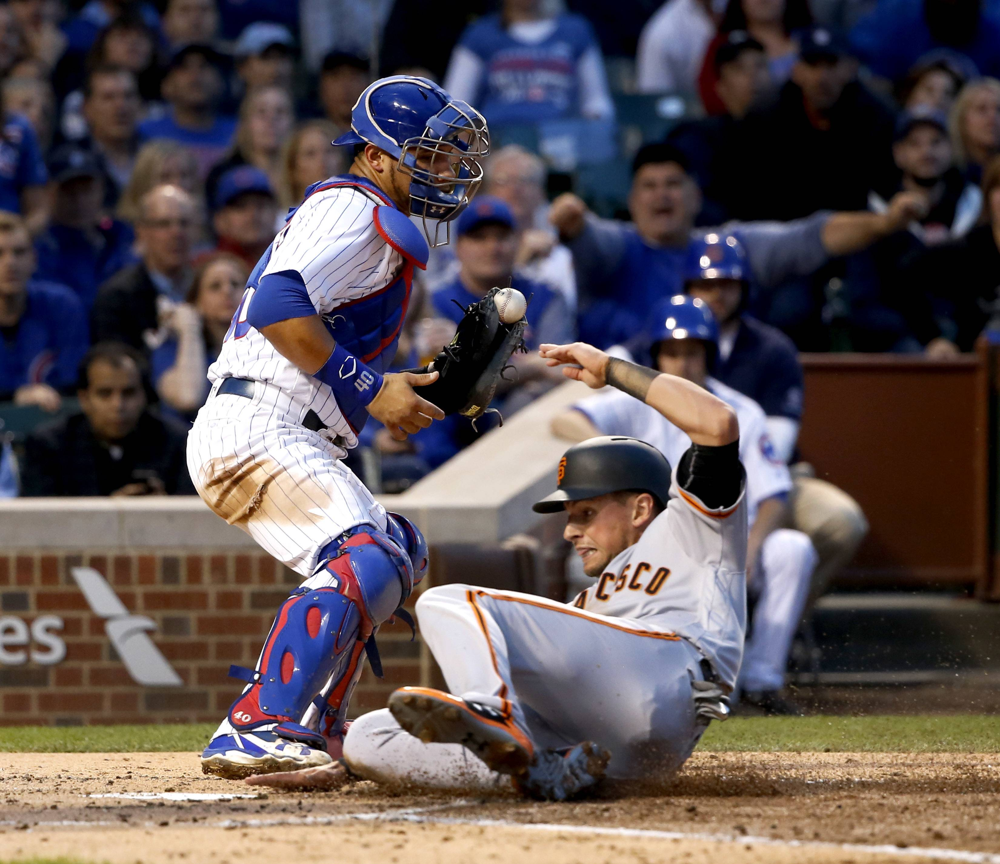 San Francisco Giants' Joe Panik, right, scores in front of Cubs catcher Willson Contreras on a single by Brandon Belt during the third inning against the Cubs on Monday in Chicago.