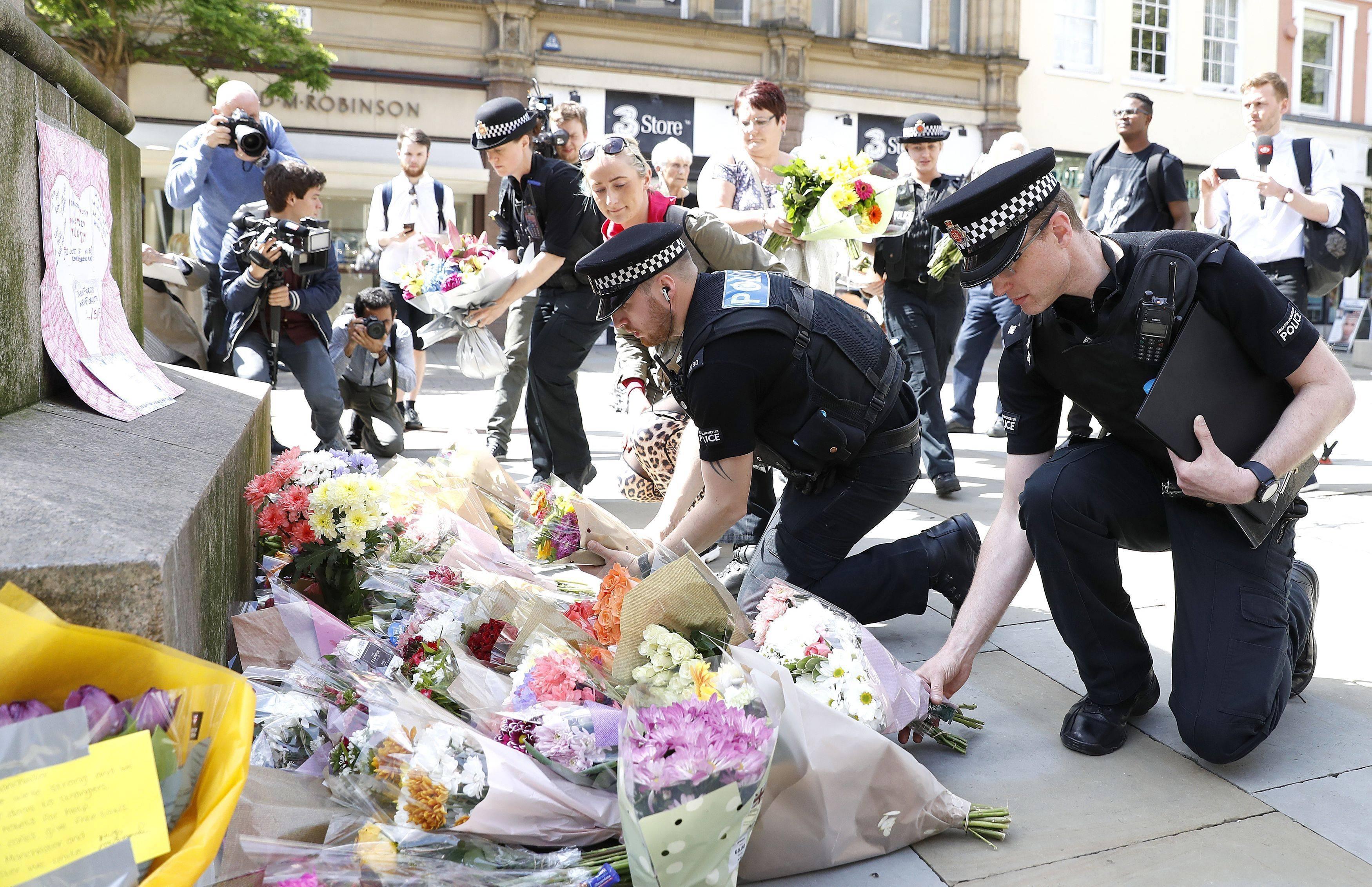 Police offices add to the flowers for the victims of Monday night pop concert explosion, in St. Ann's Square, Manchester, Tuesday May 23, 2017. A 23-year-old man was arrested in connection with Monday's Manchester concert bomb attack. The Islamic State group claimed responsibility Tuesday for the suicide attack at an Ariana Grande show that left over 20 people dead and dozens injured.