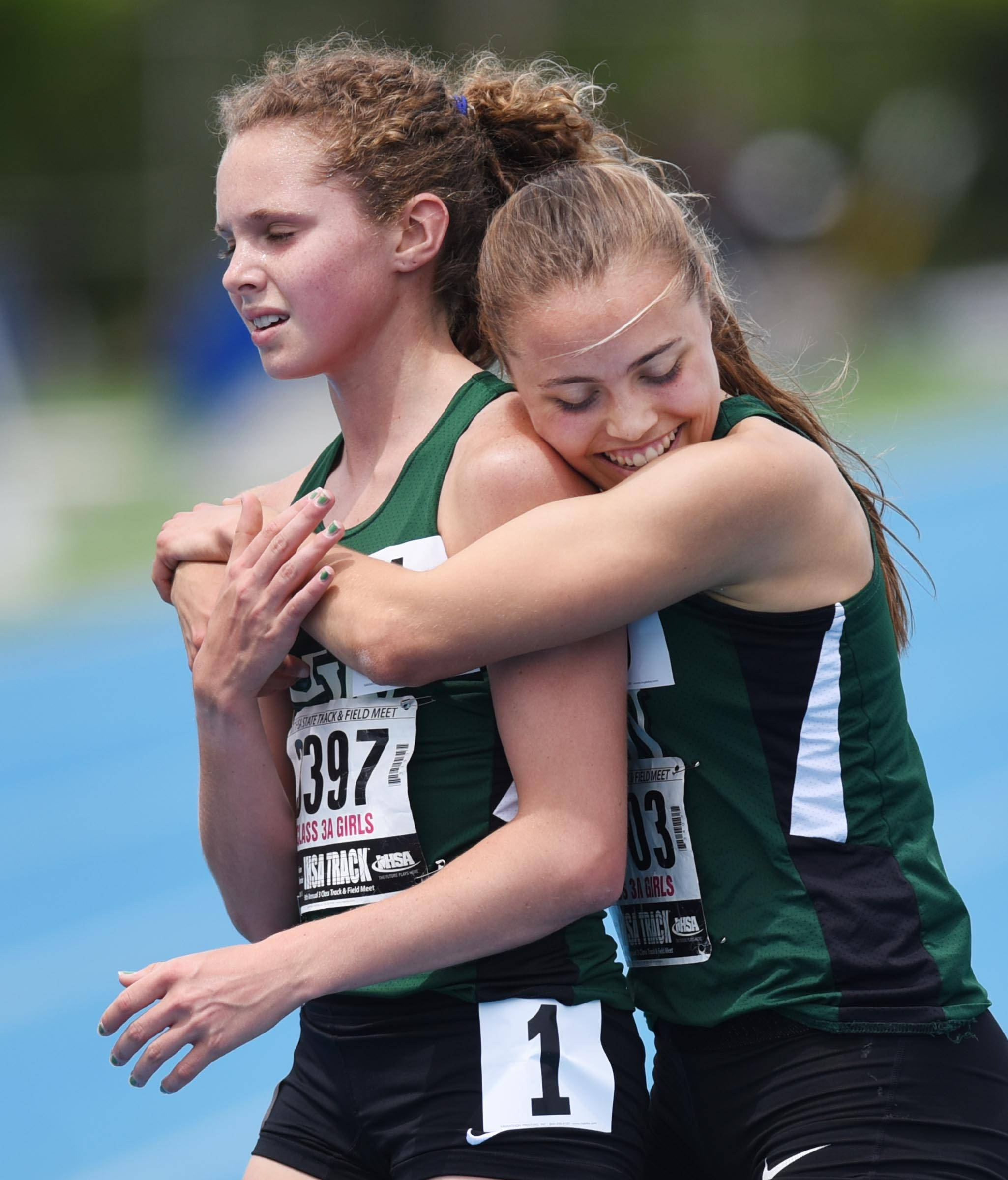 Glenbard West's Lindsey Payne hugs teammate Katelynne Hart after they placed second and first, respectively, in the Class 3A 3200-Meter Run at the state girls track and field meet finals on Saturday at Eastern Illinois University in Charleston.