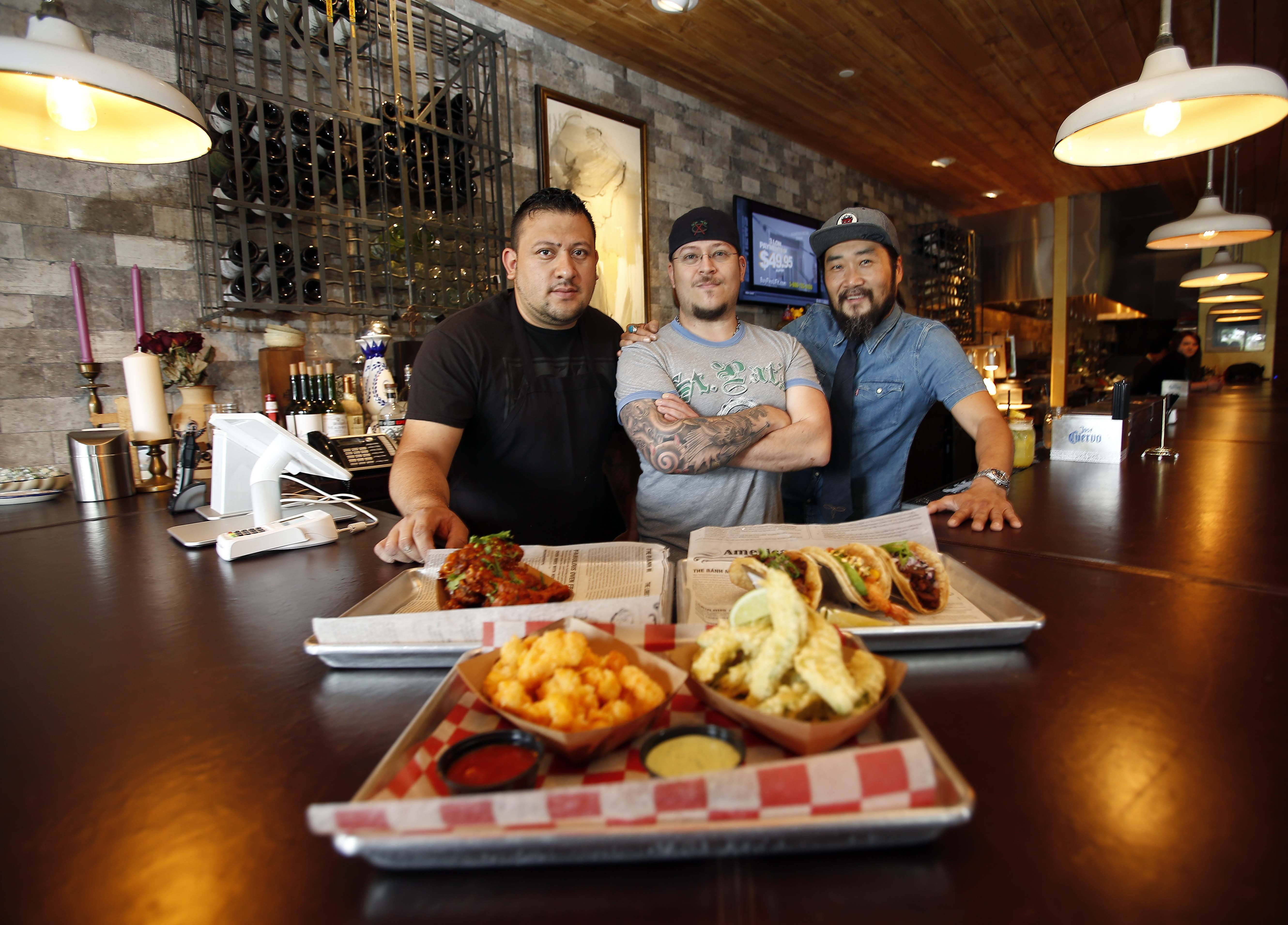 Chef Roberto Luna, left, chef Kurt Anderson and co-owner Peter Rim show off some tasty eats at El Cochino in Lake in the Hills.