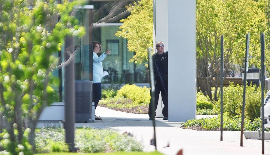A hospital employee speaks with a police officer May 13 at the Delnor Hospital emergency room entrance during a hostage situation.
