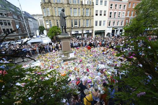 People hold a minute of silence in a square in central Manchester, England, Thursday, May 25, 2017, for the victims of the suicide attack at an Ariana Grande concert that left more than 20 people dead and many more injured, as it ended on Monday night at the Manchester Arena. (Ben Birchall/PA via AP)