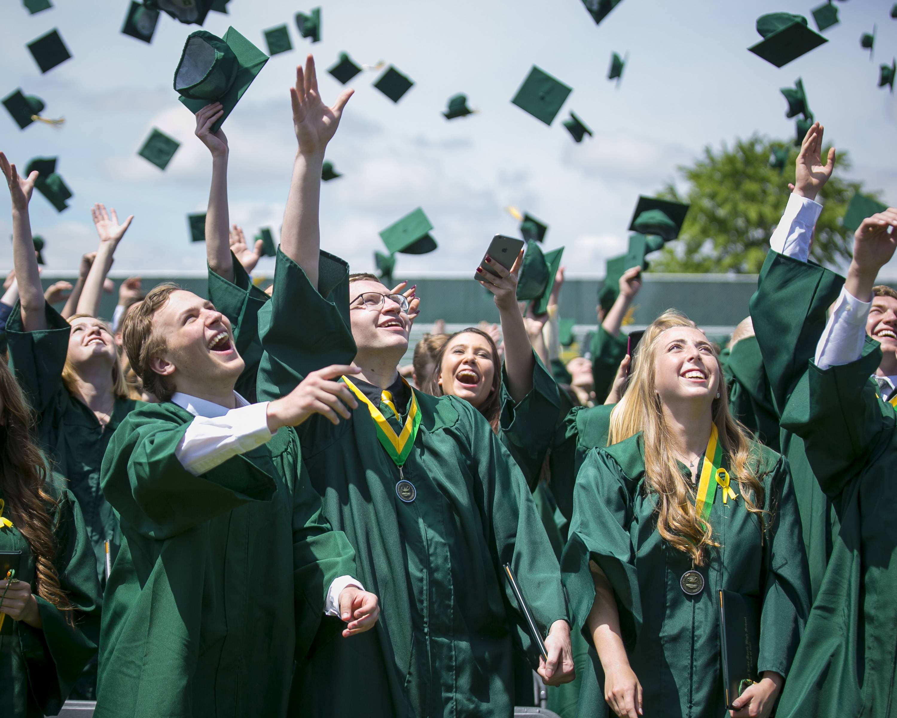 Kyle Babeti (left), Anthony Baietto, and Brittany Baker smile while watching their thrown mortarboards in the air during Crystal Lake South High School's 2017 Commencement Ceremony at Crystal Lake South High School Saturday, May 27, 2017.