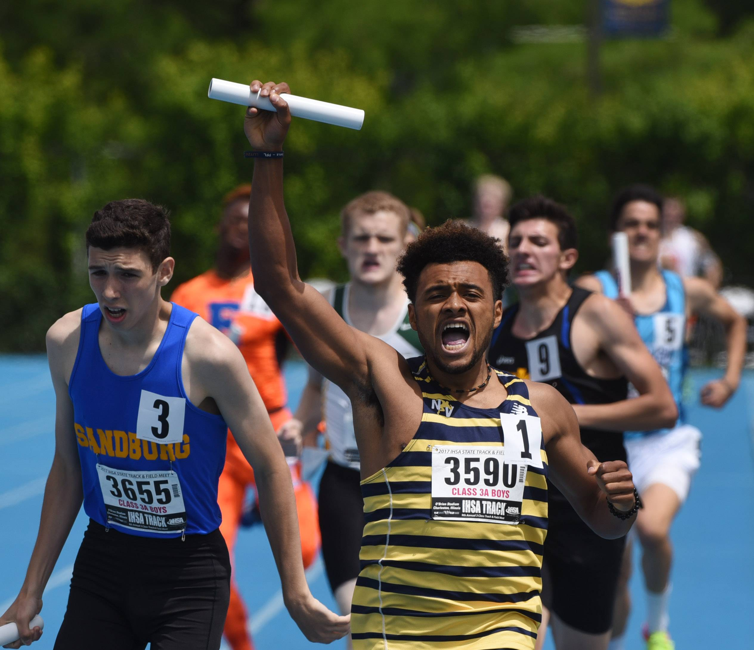 Neuqua Valley's Isaiah Robinson holds the baton high as he crosses the finish line with his team's win in the class 3A 3,200 meter relay during the boys state track and field finals at Eastern Illinois University in Charleston Saturday.