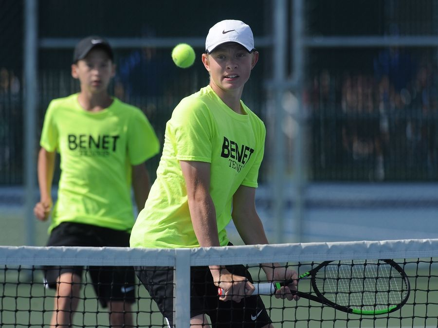 Benet's Casey Schrader eyes the ball as his partner Danny McGuigan backs him up in the Class 1A Doubles boys semifinals tennis at Hersey on Saturday. They were playing Dunlap's Steven Chacko and David Wu of Dunlap High School.