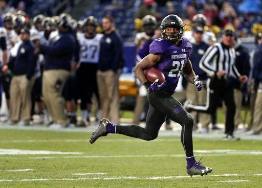FILE- In this Dec. 28, 2016, file photo, Northwestern running back Justin Jackson (21) runs for a touchdown against the Pittsburgh during the third quarter of the Pinstripe Bowl NCAA college football game in New York. Over the last three seasons, no Power Five team has relied on a running back as much as Northwestern has relied on Jackson, an old-school workhorse at a time of tailback-by-committee and early NFL draft entrants. (AP Photo/Julie Jacobson, File)