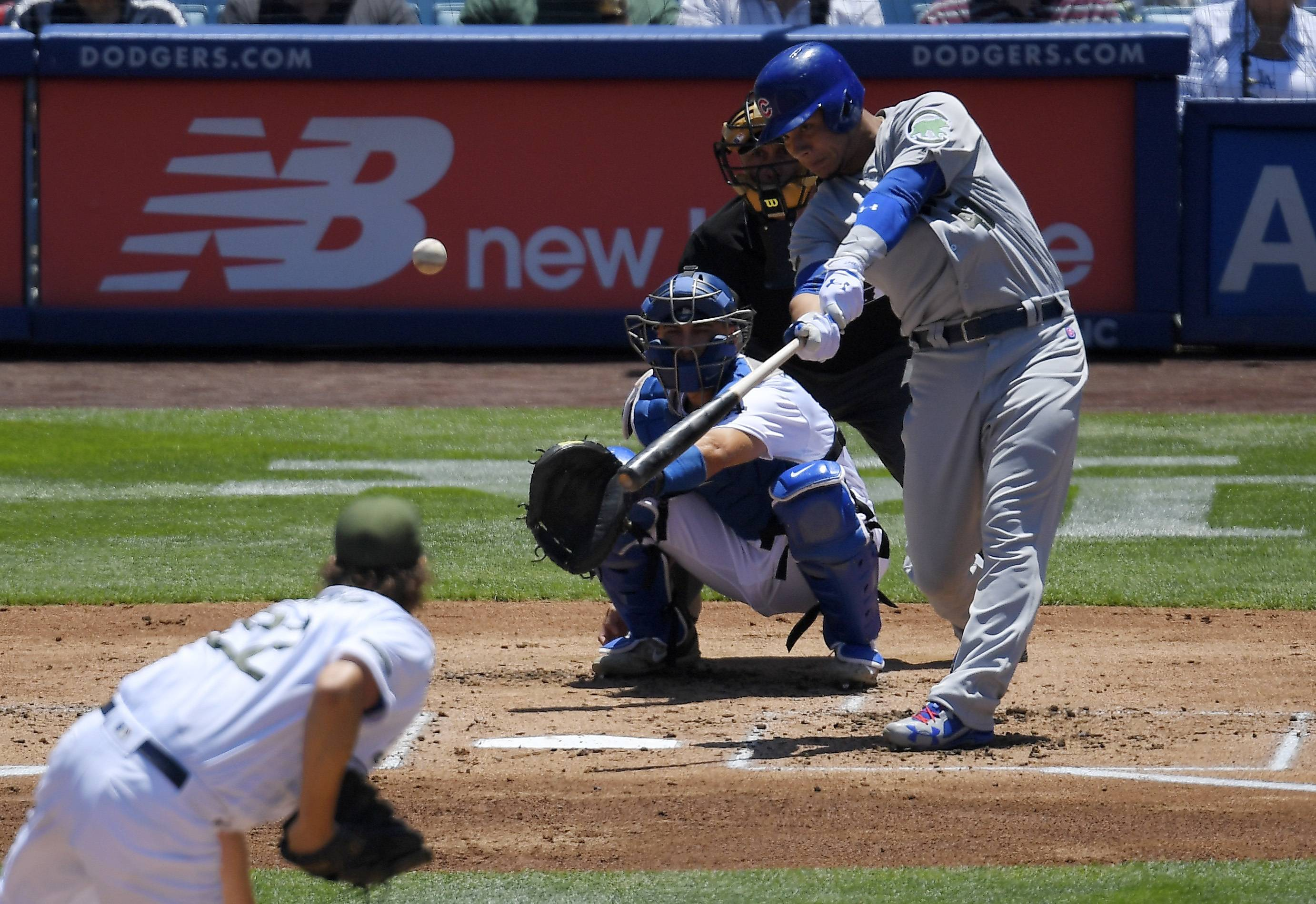 Chicago Cubs' Willson Contreras, right, hits a solo home run as Los Angeles Dodgers starting pitcher Clayton Kershaw, left, watches along with catcher Austin Barnes, second from left, and home plate umpire Dan Iassogna during the second inning of a baseball game, Sunday, May 28, 2017, in Los Angeles.