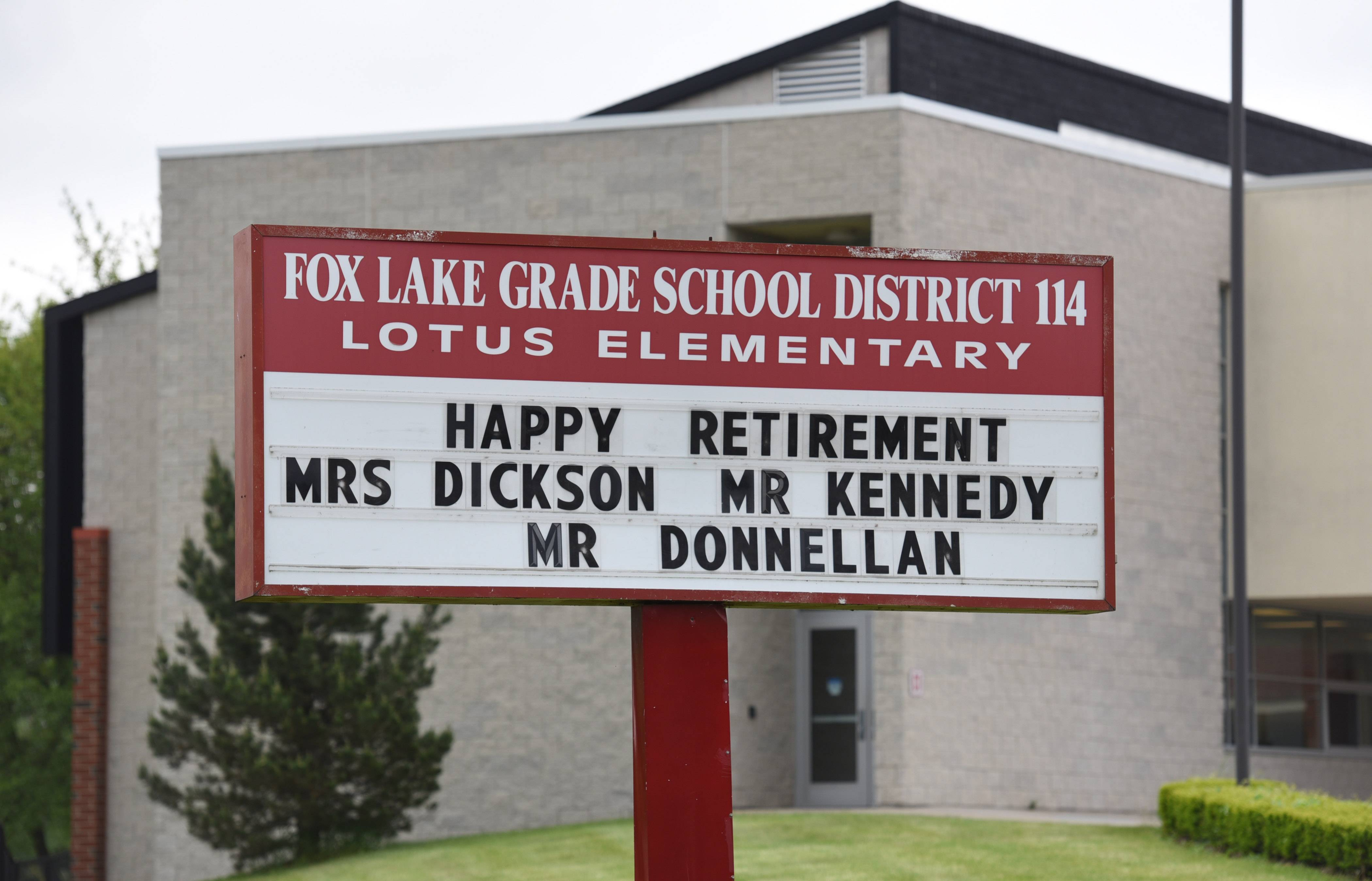 Fox Lake Grade School District 114 Superintendent John Donnellan shares retirement well wishes on a sign with two district teachers.