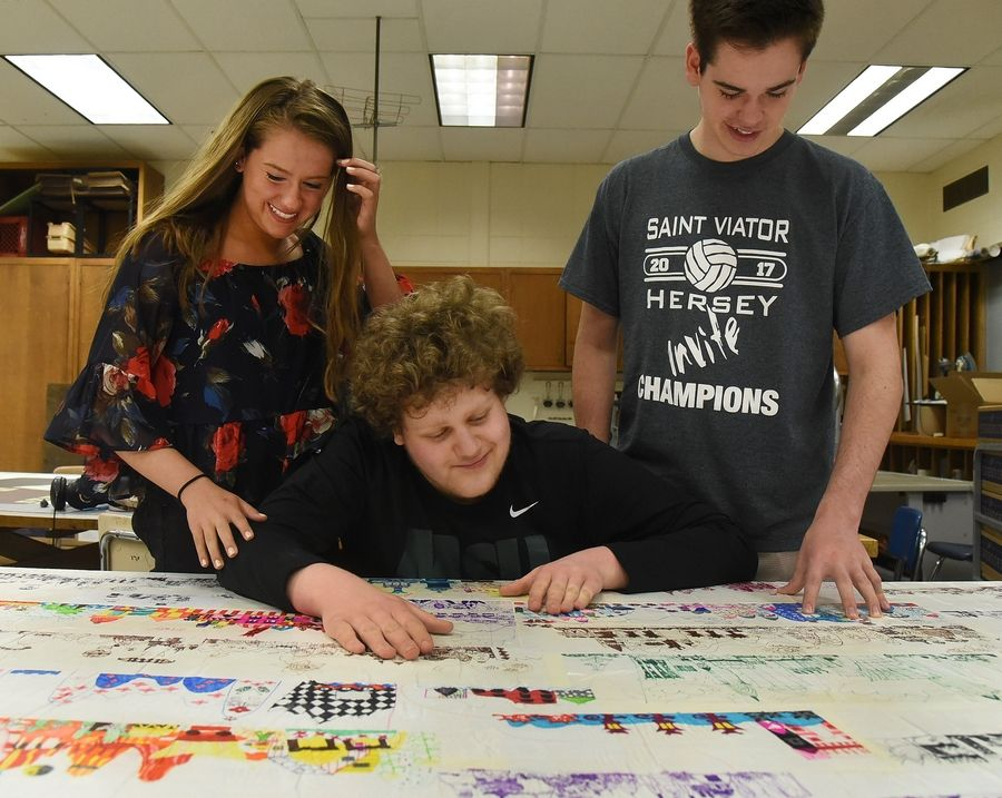 Johnny Reisel, center, and his two siblings, Maggie and Vince, with a mural made up of Johnny's pictures. It will be installed later this summer as part of an expanded Career Life Skills wing at Hersey High School.