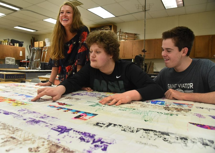 Johnny Reisel, center, and his two siblings, Maggie and Vince, look over a mural made up of Johnny's pictures.