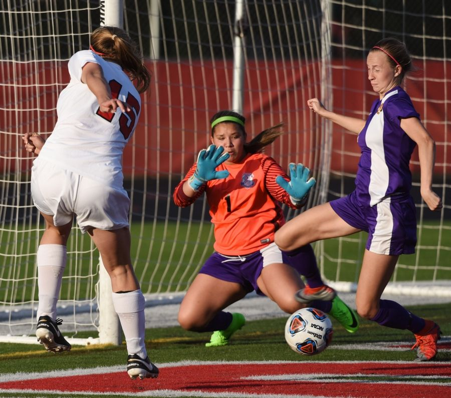 Barrington's Ellie Stodola, left, kicks the ball past Rockton Hononegah goalkeeper Alyssa Darling and Lauren Phillips for a second-half goal during the Class 3A girls soccer Barrington supersectional Tuesday.