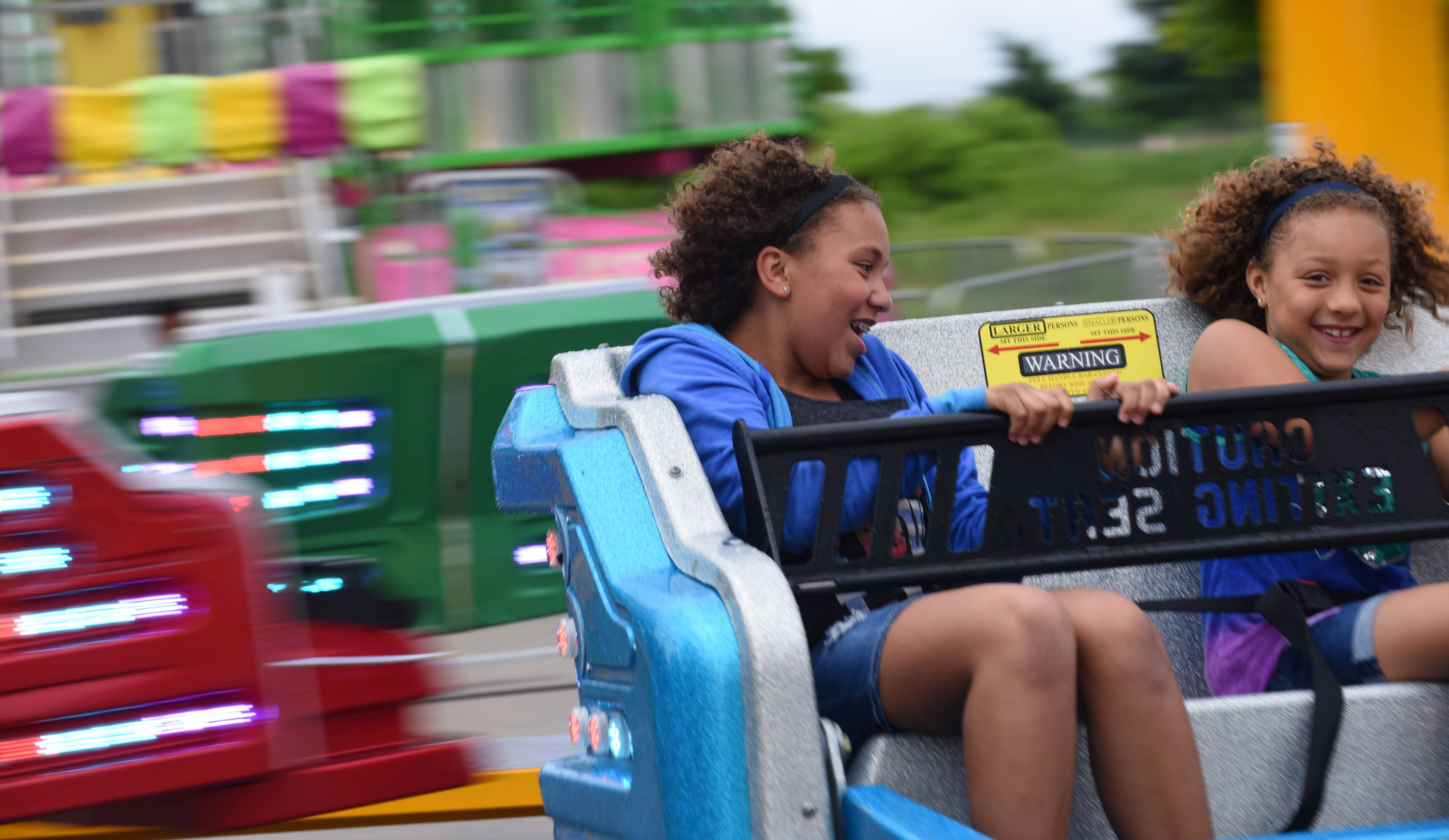 "Sisters Sydney, 12, and Madison Carter, 8, of Gilberts ride ""Sizzler"" at the Gilberts Community Days festival. Their father, Max Carter, said he and the girls have been coming to the carnival for five years."