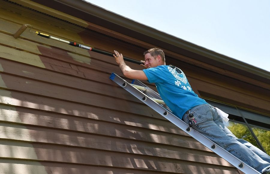 Sales representative Dan Zalewski of Schaumburg applies a new coat of paint to the side of a Little City building. Volunteers from local Sherwin-Williams stores painted the exteriors of a new Little City apartment community Thursday.