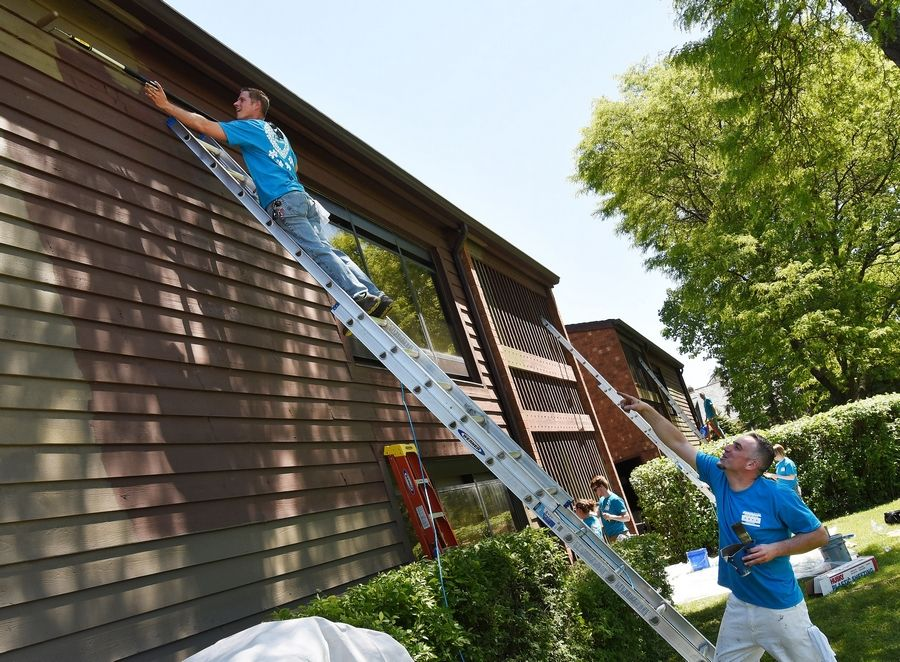 Sales representatives Dan Zalewski of Schaumburg, left, and Rafal Czapla of Lombard apply a new coat of paint to the side of a Little City building. Volunteers from local Sherwin-Williams stores painted the exteriors of a new Little City apartment community Thursday.