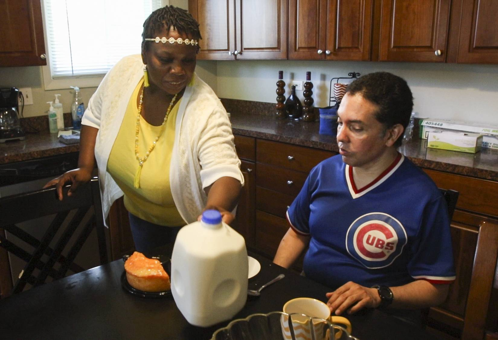 Direct Support Professional Essie Martin gives Eddie Arroyo his daily snack at the Ray Graham Association community-based home in Lombard. Ray Graham and other social service agencies want the state to provide better funding for caregiver wages.