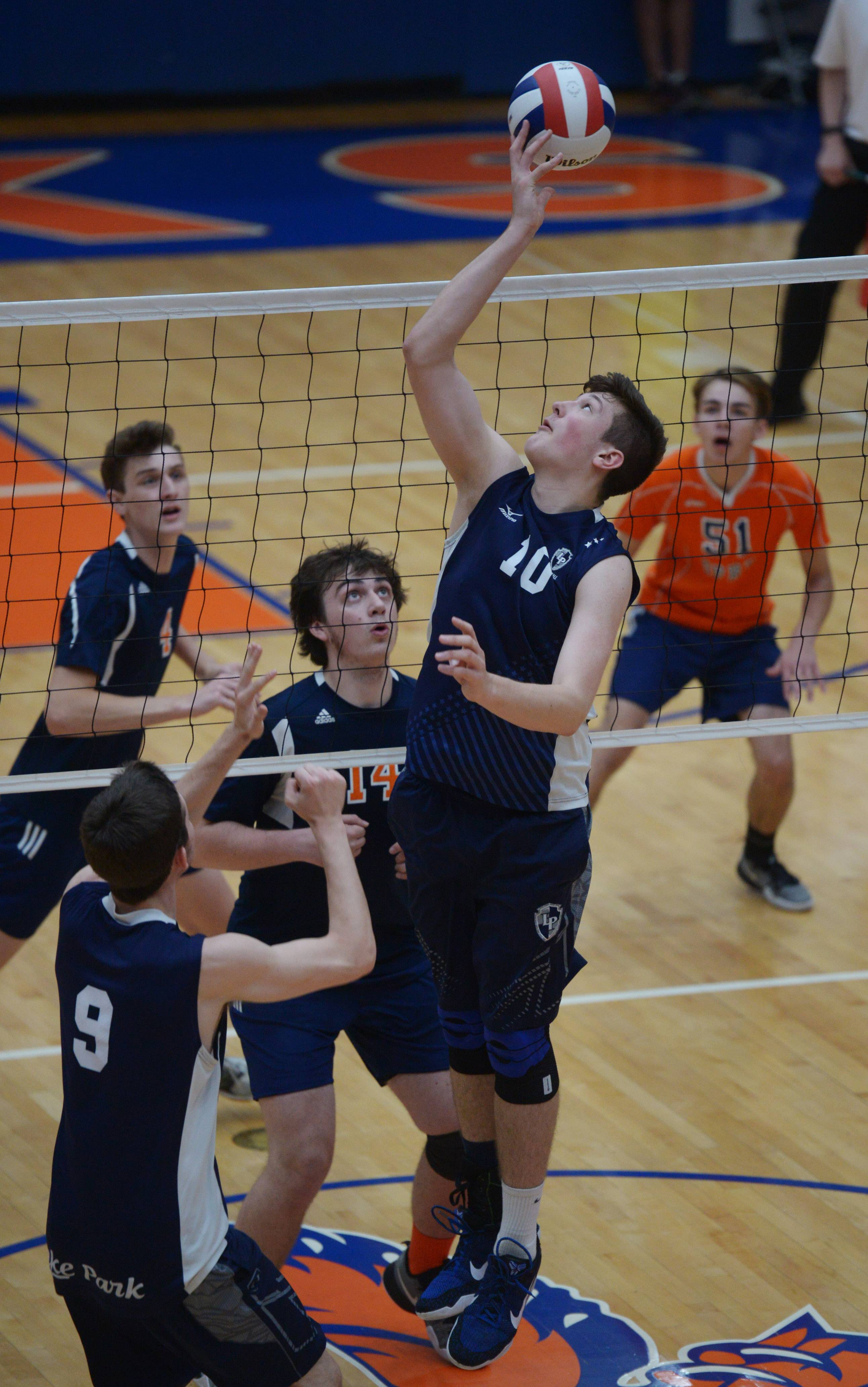Lake Park setter Justin Yost (10) tips the ball backward over the net in front of Oak Park-River Forest's Ben Shinners (14) during the boys volleyball state quarterfinals at Hoffman Estates High School Friday.