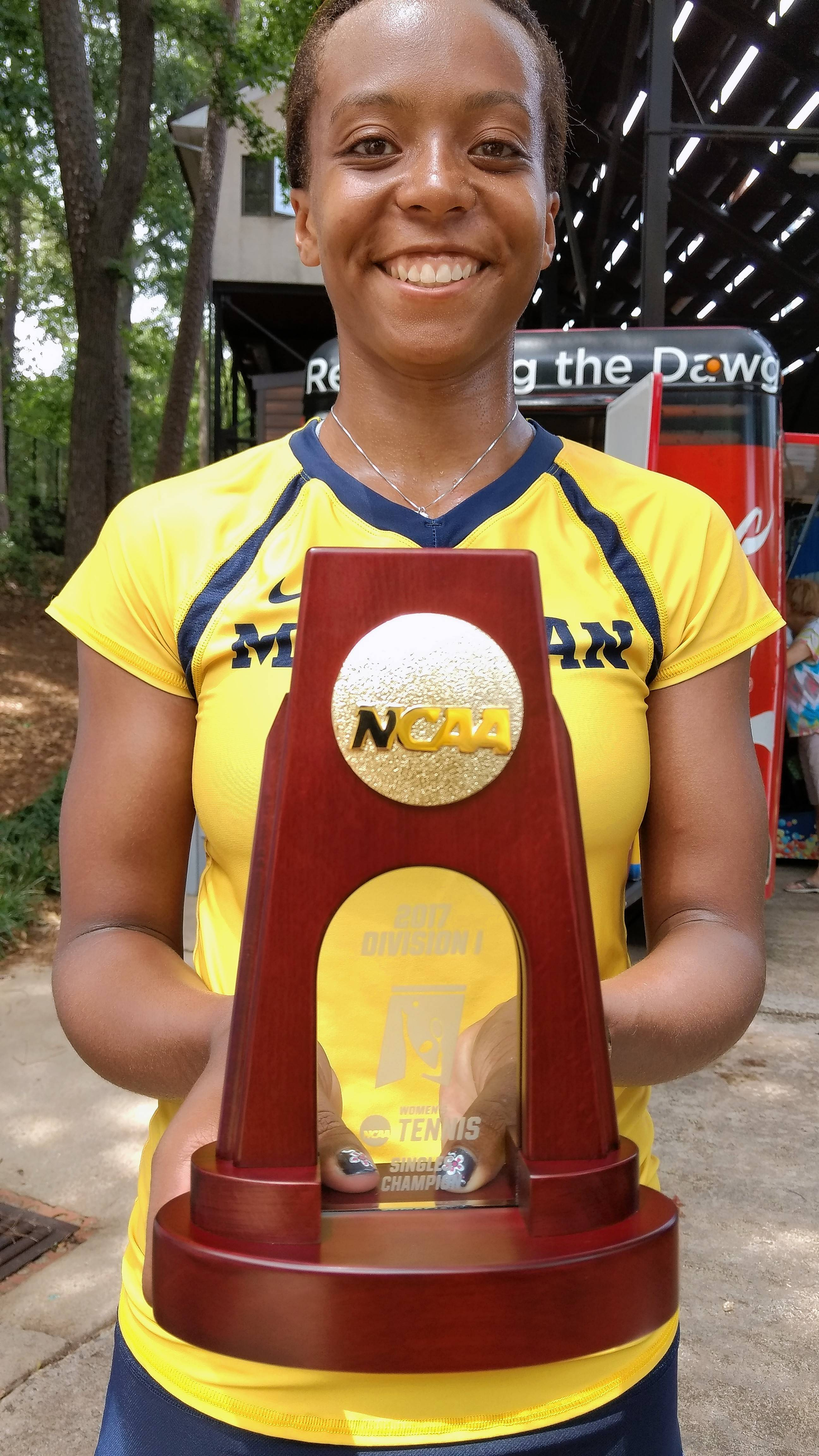 Michigan sophomore tennis player Brienne Minor, a Mundelein native, displays the NCAA Championship trophy she earned in women's singles. Minor was unranked entering the tournament.