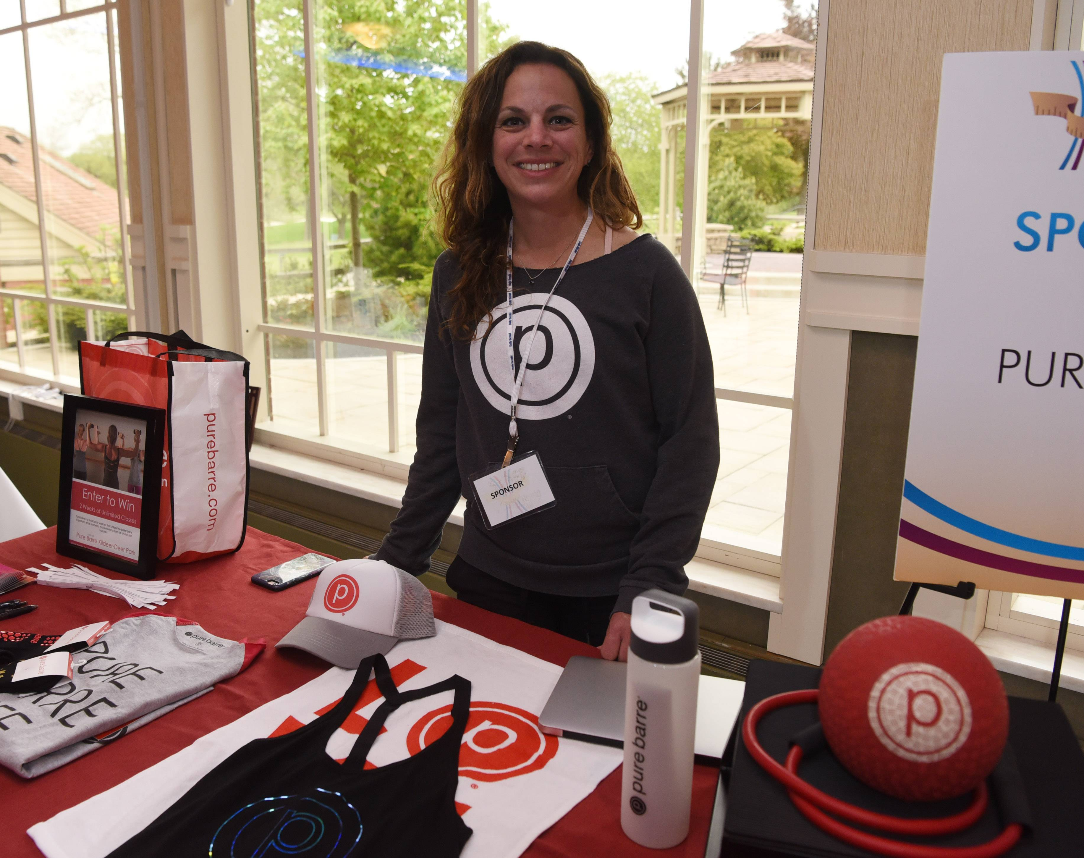 Faith Anne Wade, owner of Pure Barre, stands at her table during the finale of the Fittest Loser competition, held at Chandler's Banquets in Schaumburg Tuesday.