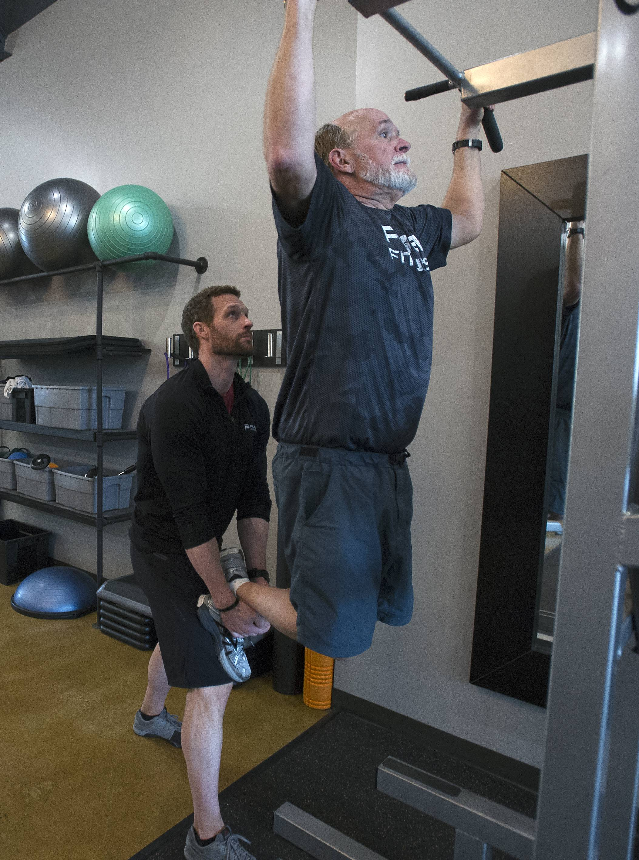 Russ Page of Antioch shows off his dramatic weight loss of almost 50 pounds after many weeks at Push Fitness in Schaumburg. He does a series of pull ups with his trainer Josh Steckler, owner of Push Fitness.