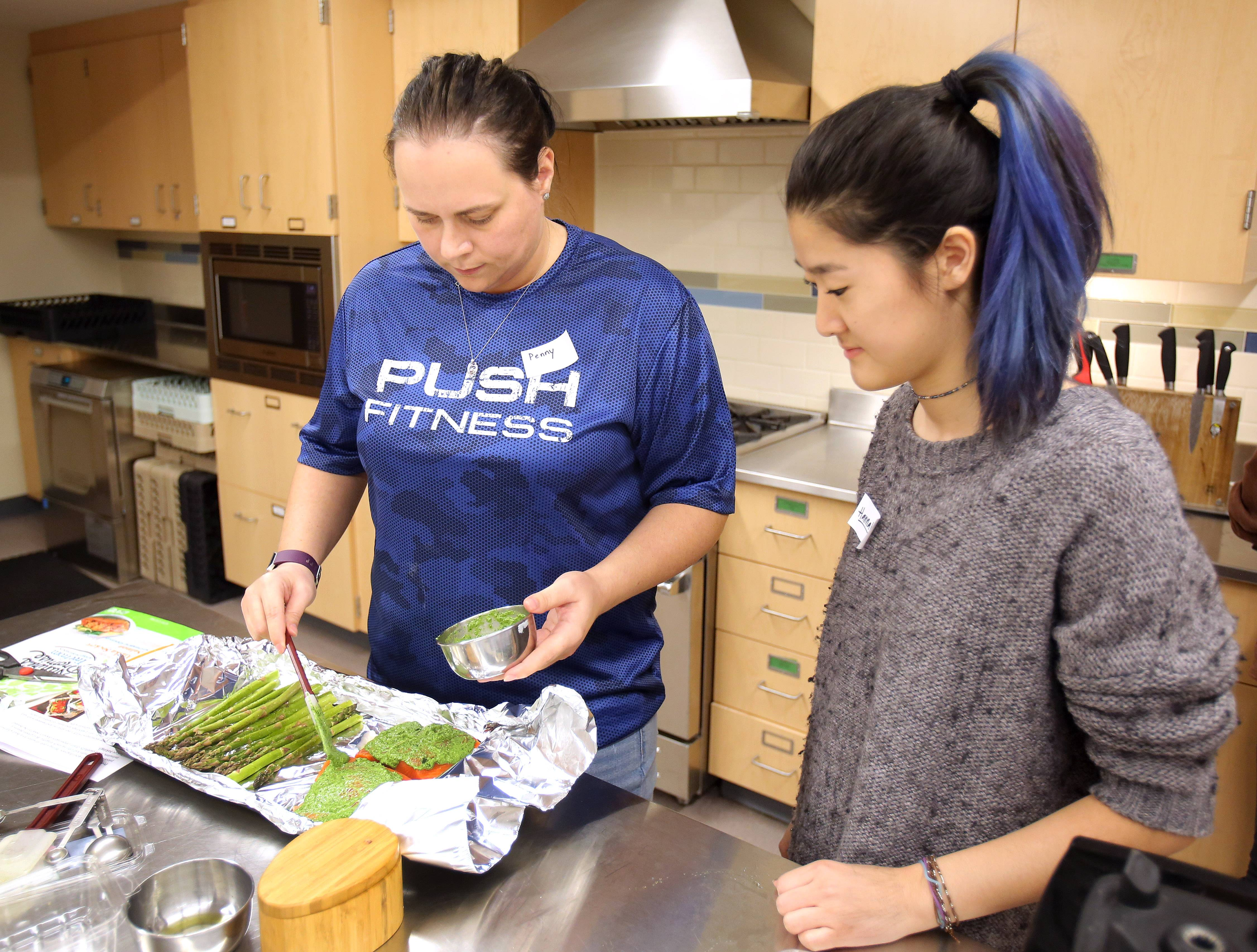 Fittest Loser contestant Penny Brown of Fox Lake, left, prepares dinner with 16-year-old Hannah Choh during a healthy cooking seminar put on by members of the Food Revolution Club at Stevenson High School in Lincolnshire.