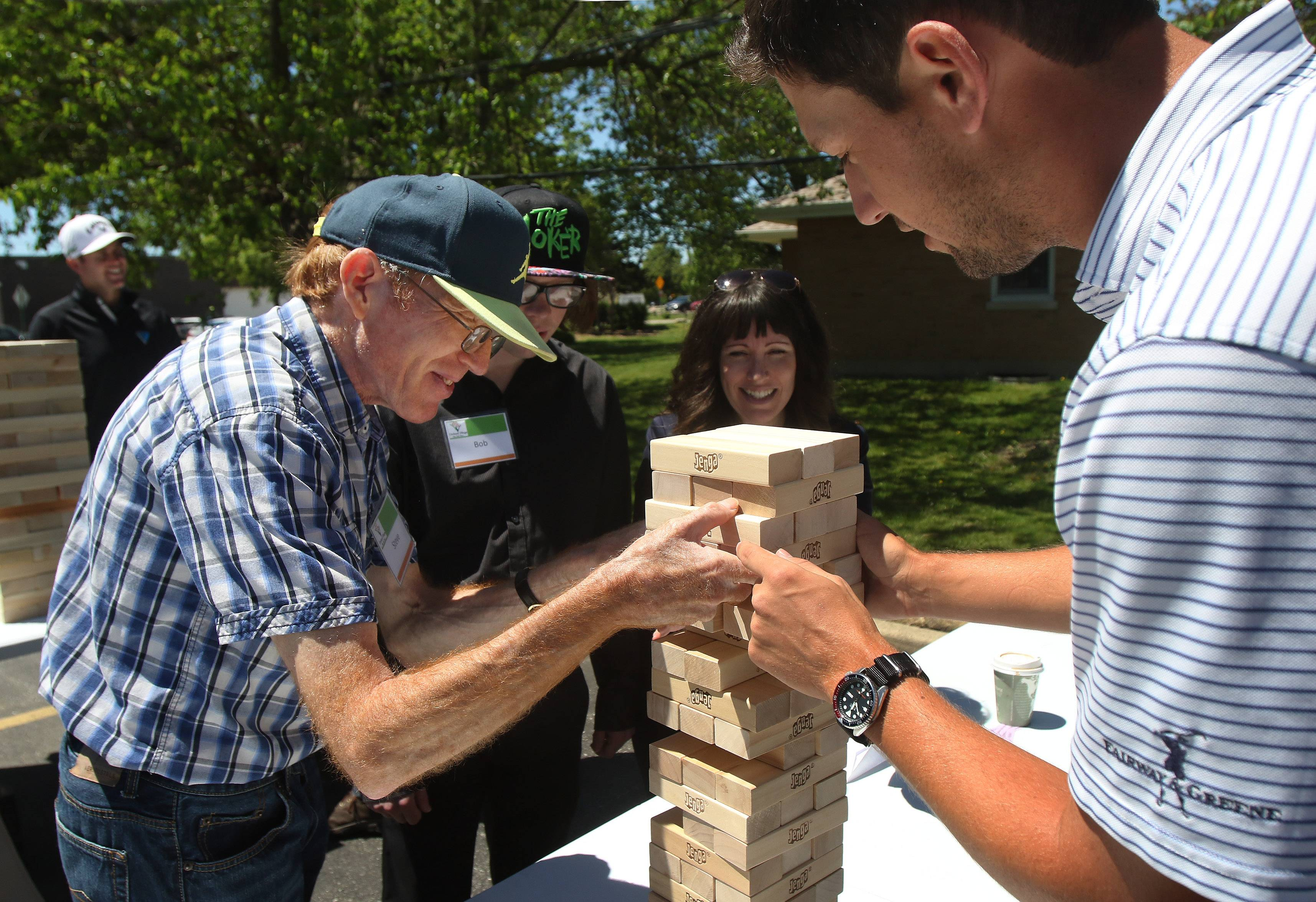 Golfer Brad Hopfinger of Lake Forest, right, helps Orchard Village resident Steve Grant with a piece as they play Jenga on Tuesday at the Skokie home for people with developmental disabilities.