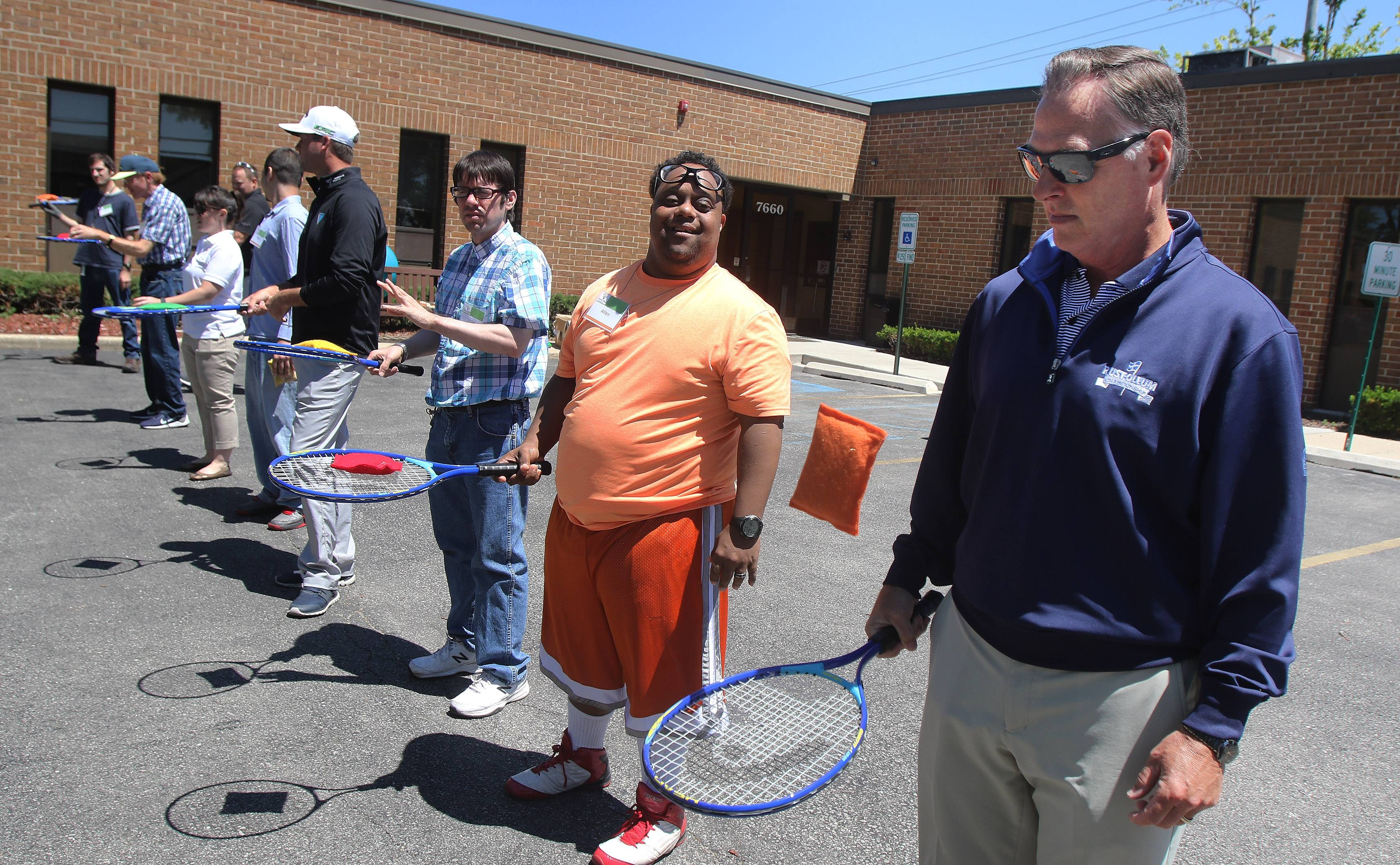 Rust-Oleum President and COO Tom Reed, right, joined golfers and residents to play games of adaptive tennis Tuesday.