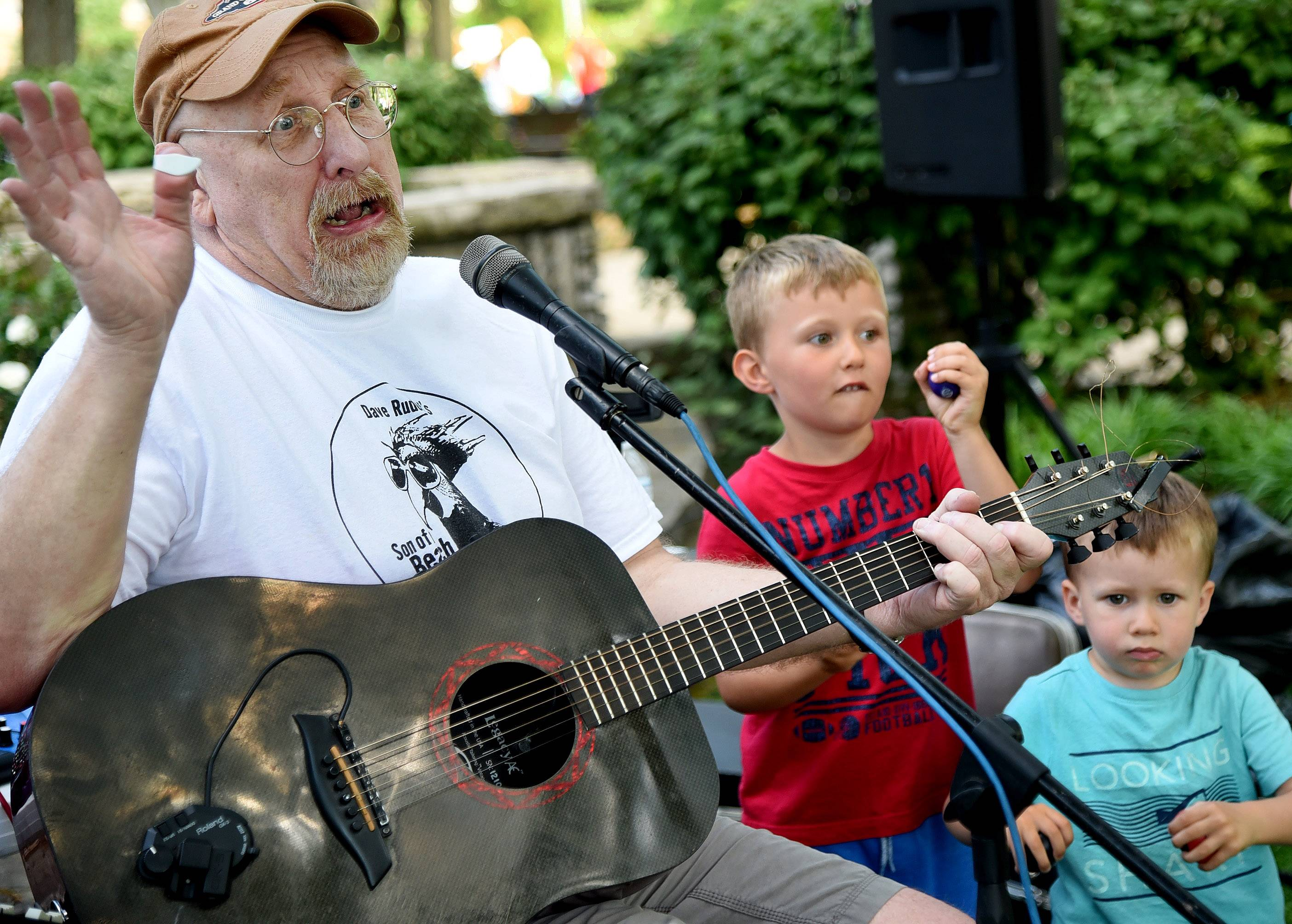Entertainer Dave Rudolf recruits a couple of friends, Brad and Ben Bristol of Arlington Heights, to help him with a tune Friday at Picnic in the Park at North School Park in Arlington Heights.