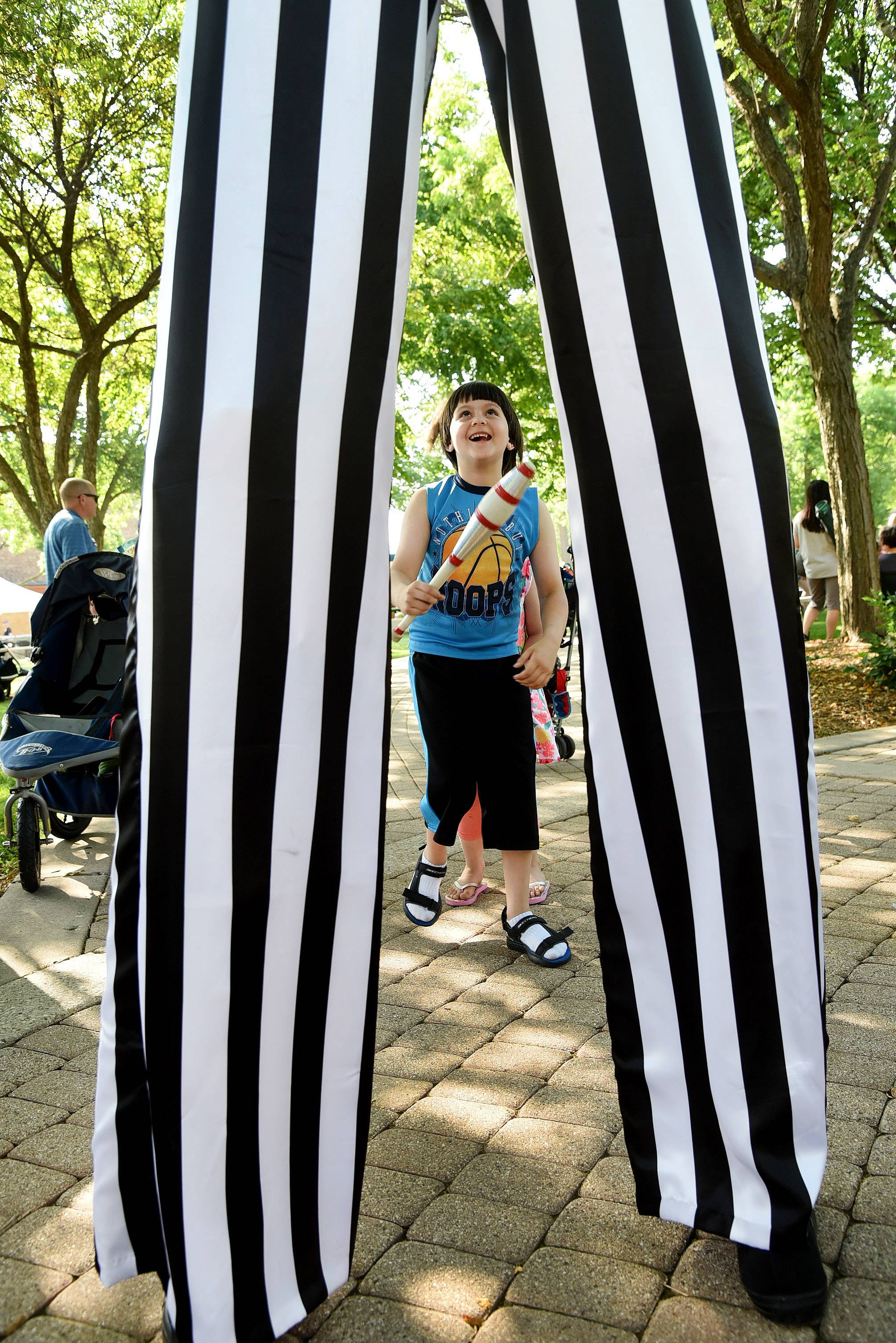 Isaiah Mulhall, 7, of Arlington Heights helps out juggler on stilts Jason Kollum Friday at Picnic in the Park at North School Park in Arlington Heights.