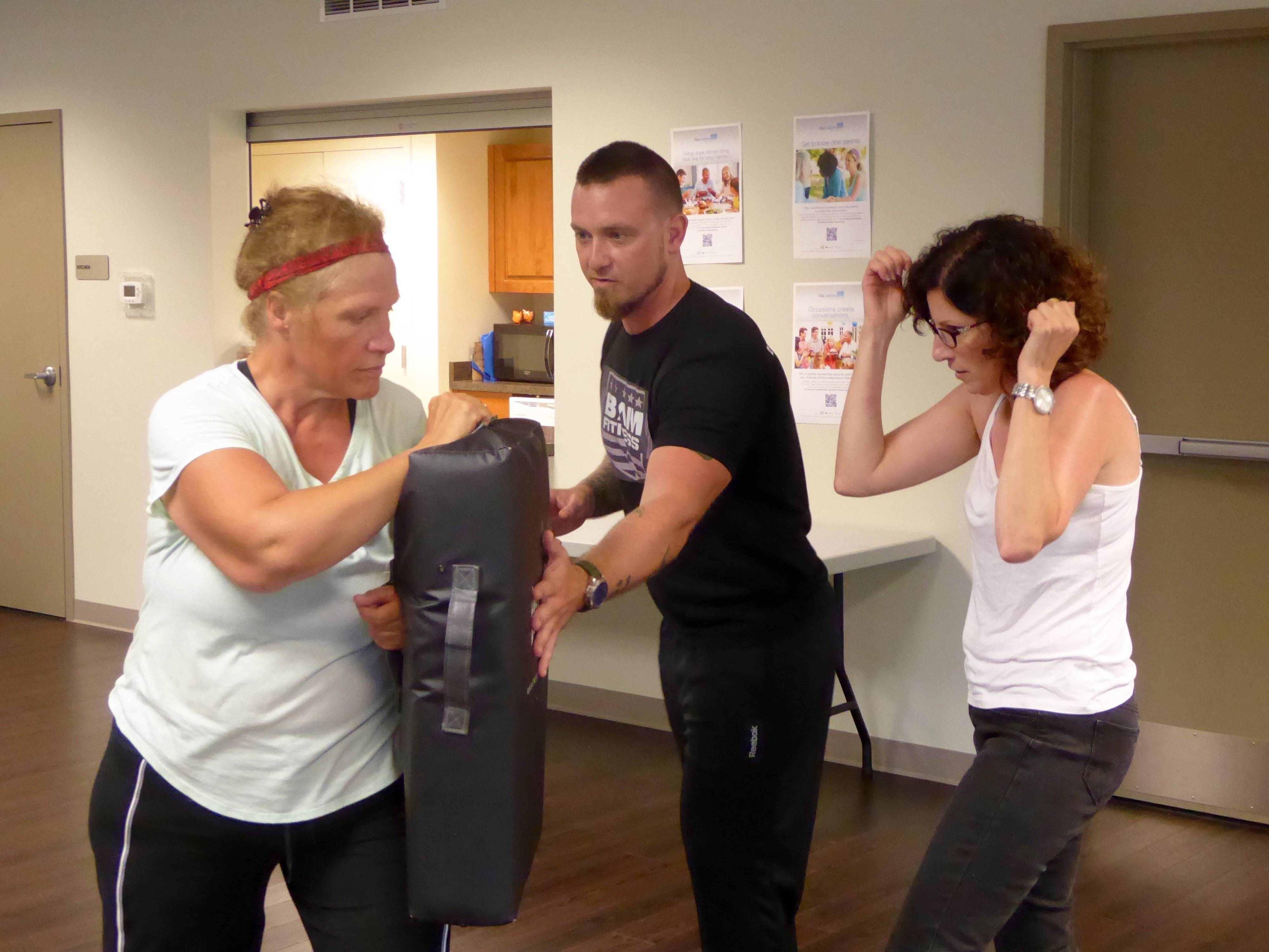 Personal trainer Bill Miller, of Bam Fitness, instructs resident Debbie Jurf and Ela Township Social Worker Roberta Smith on self-defense tactics during a program hosted by Ela Township Community Family Services on June 8.​Ela Township