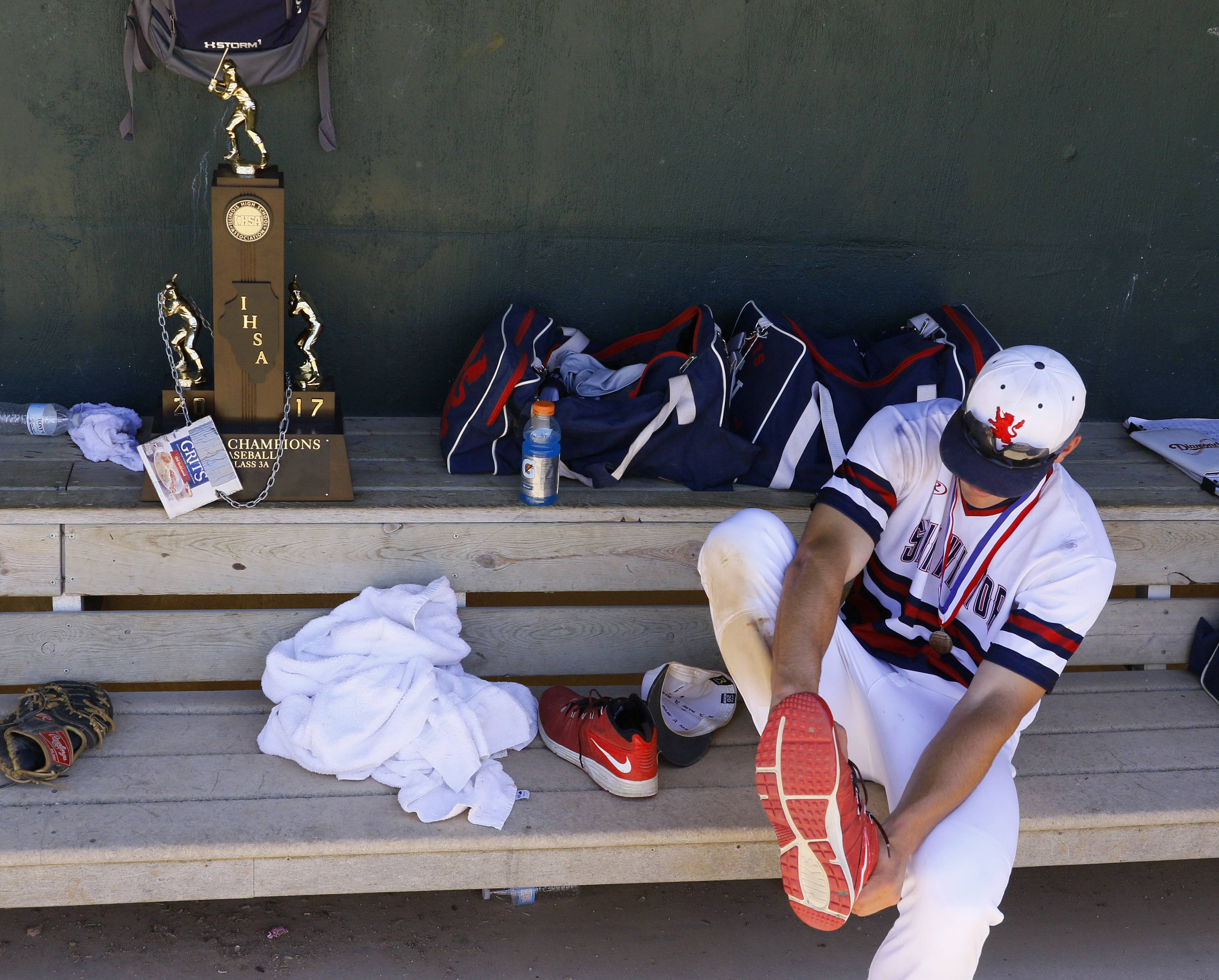 St. Viator's Cole Kmet changes his shoes next to the Class 3A baseball state championship trophy on Saturday in Joliet.