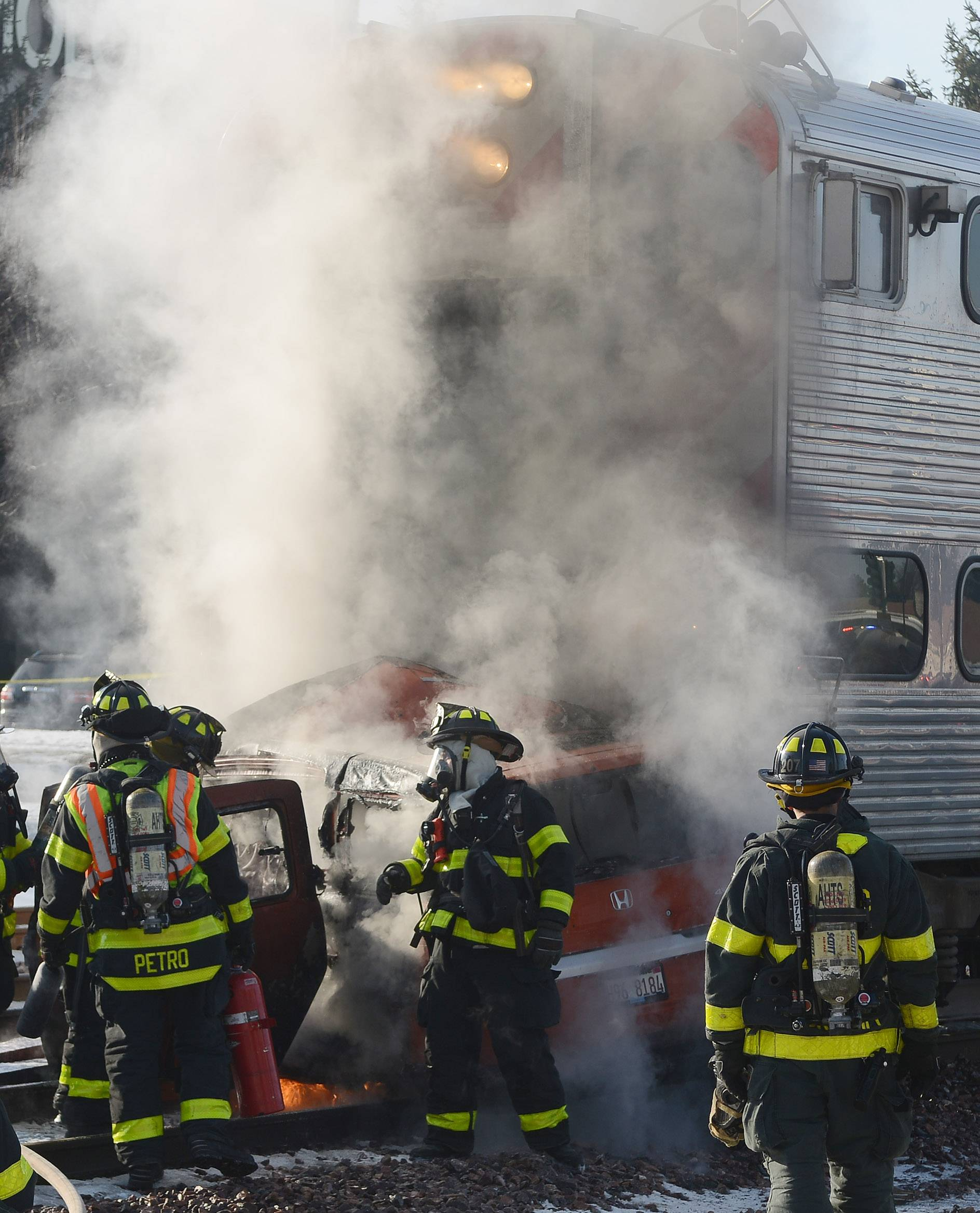 Arlington Heights firefighters extinguish a fire that resulted after inbound Union Pacific Northwest Line train number 646 struck a car at Euclid Avenue in Arlington Heights. The train came to a stop at Walnut Avenue with the burning car at the front of the lead coach.