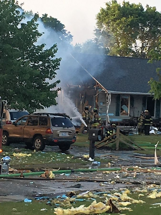 Fire crews work the scene of an explosion Sunday morning that resulted in a fire at four houses in the 500 block of 7th Avenue in Marengo.