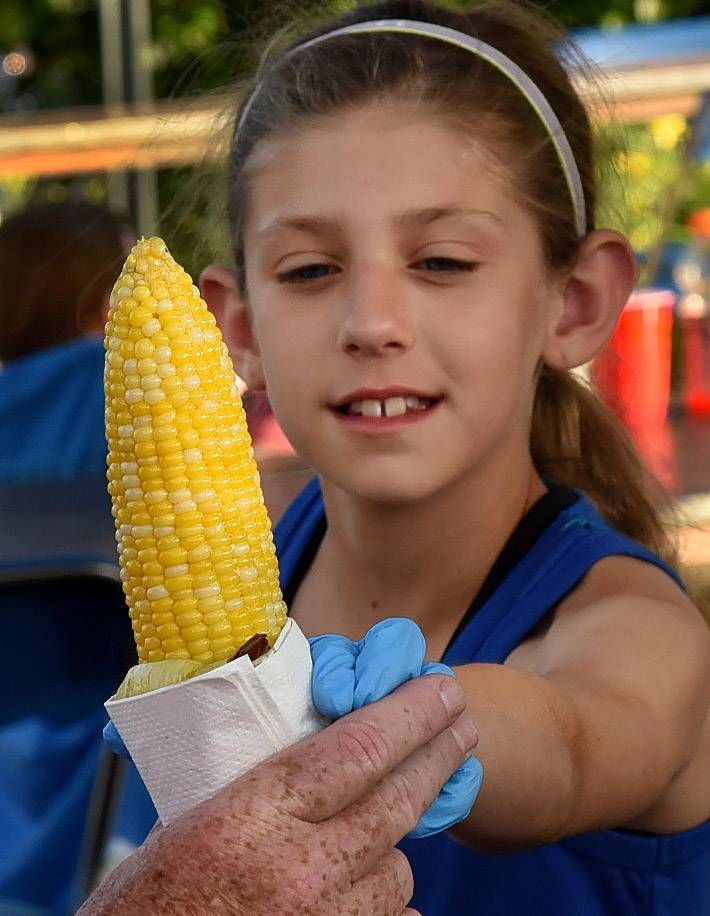 Mayah Sullivan serves up corn while helping out the Elk Grove Fire Department last year at Rotary Fest, the first big festival of summer in the Northwest suburbs.