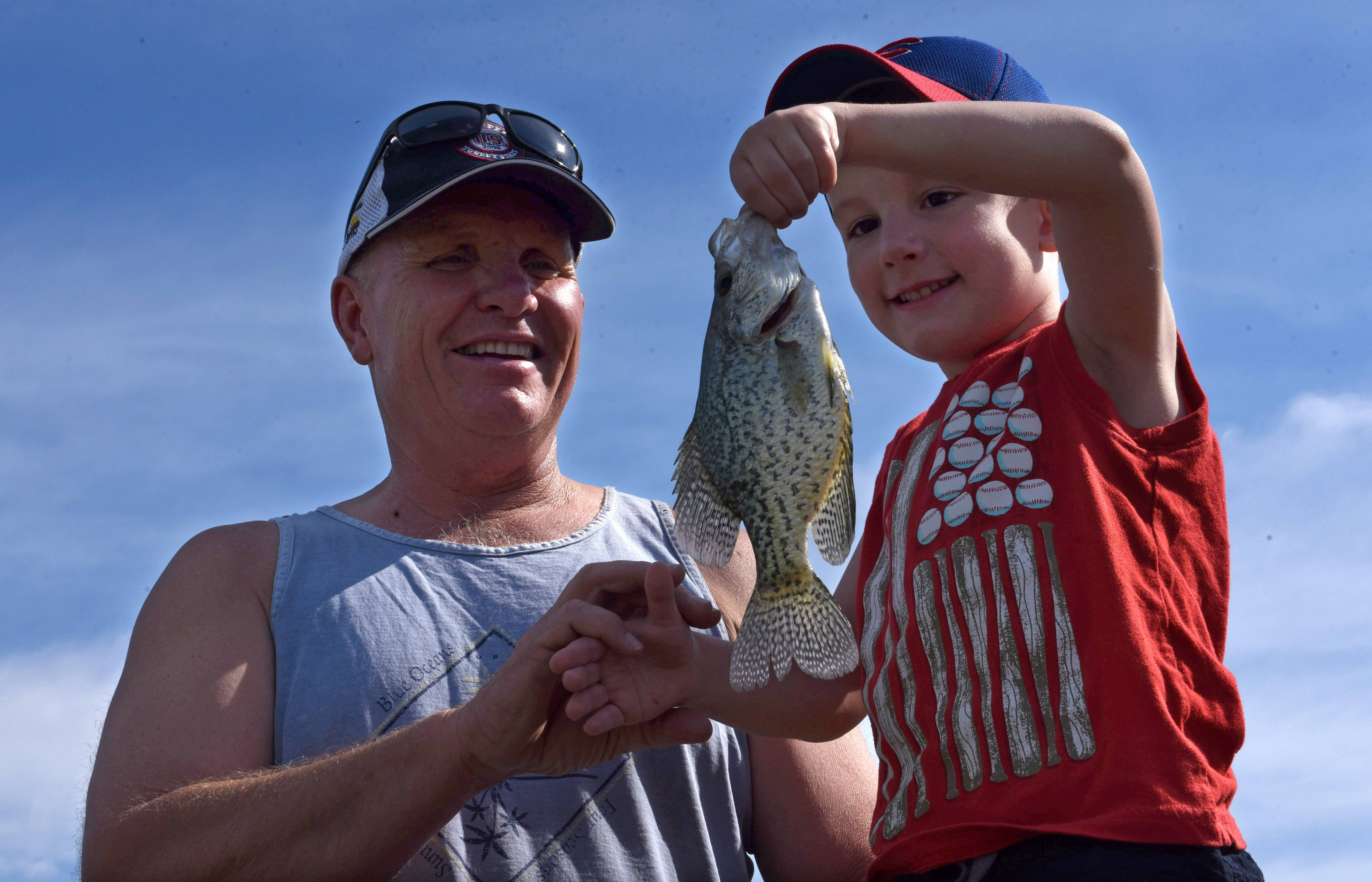 Vincent Galassi, 5, of South Elgin, holds up his recently-caught crappie alongside his grandfather, Mike Lifka of South Elgin, during the Tuna Kahuna fishing derby last year in South Elgin. Both South Elgin and Batavia are holding fishing derbies this weekend.