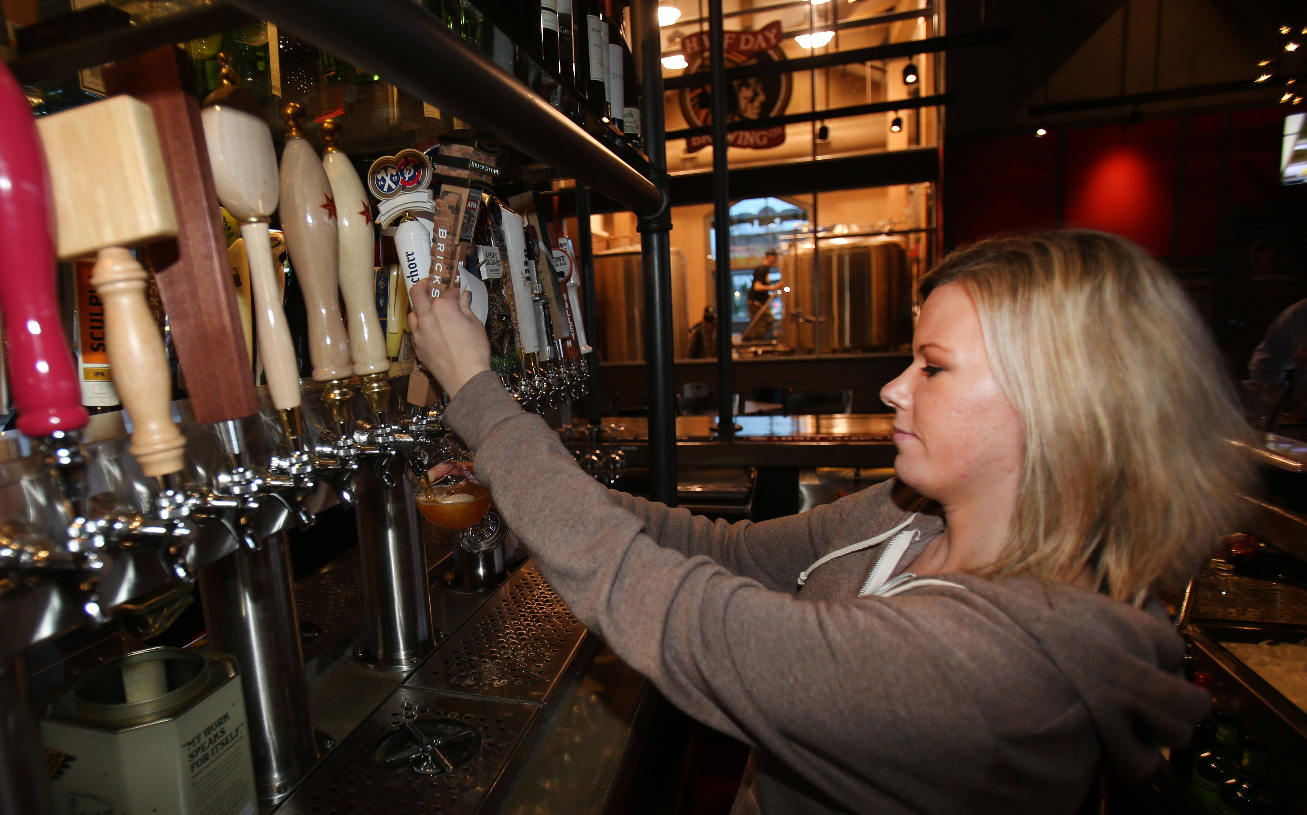 Bartender Amanda McDuffie pours a beer at Half Day Brewing Company in Lincolnshire. The establishment is among those tourism officials hope will draw visitors to Lake County.
