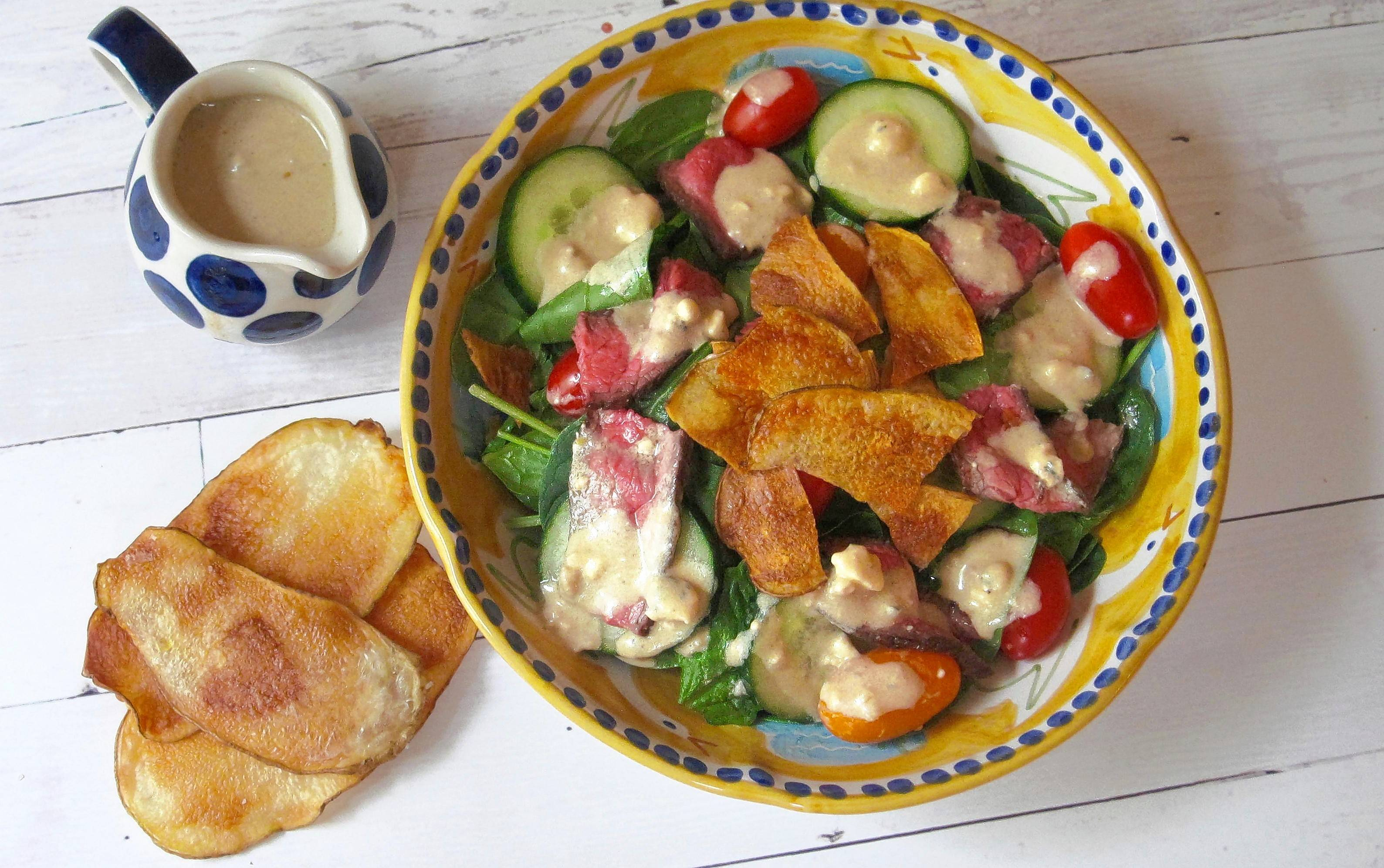 A warm steak and potato chip salad with blue cheese dressing. All the richness of a steak with bluecheese accents and even potato chips, all as a salad.